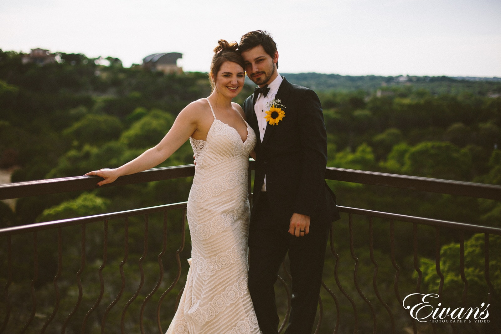 man in black suit and woman in white wedding dress holding on railings during daytime