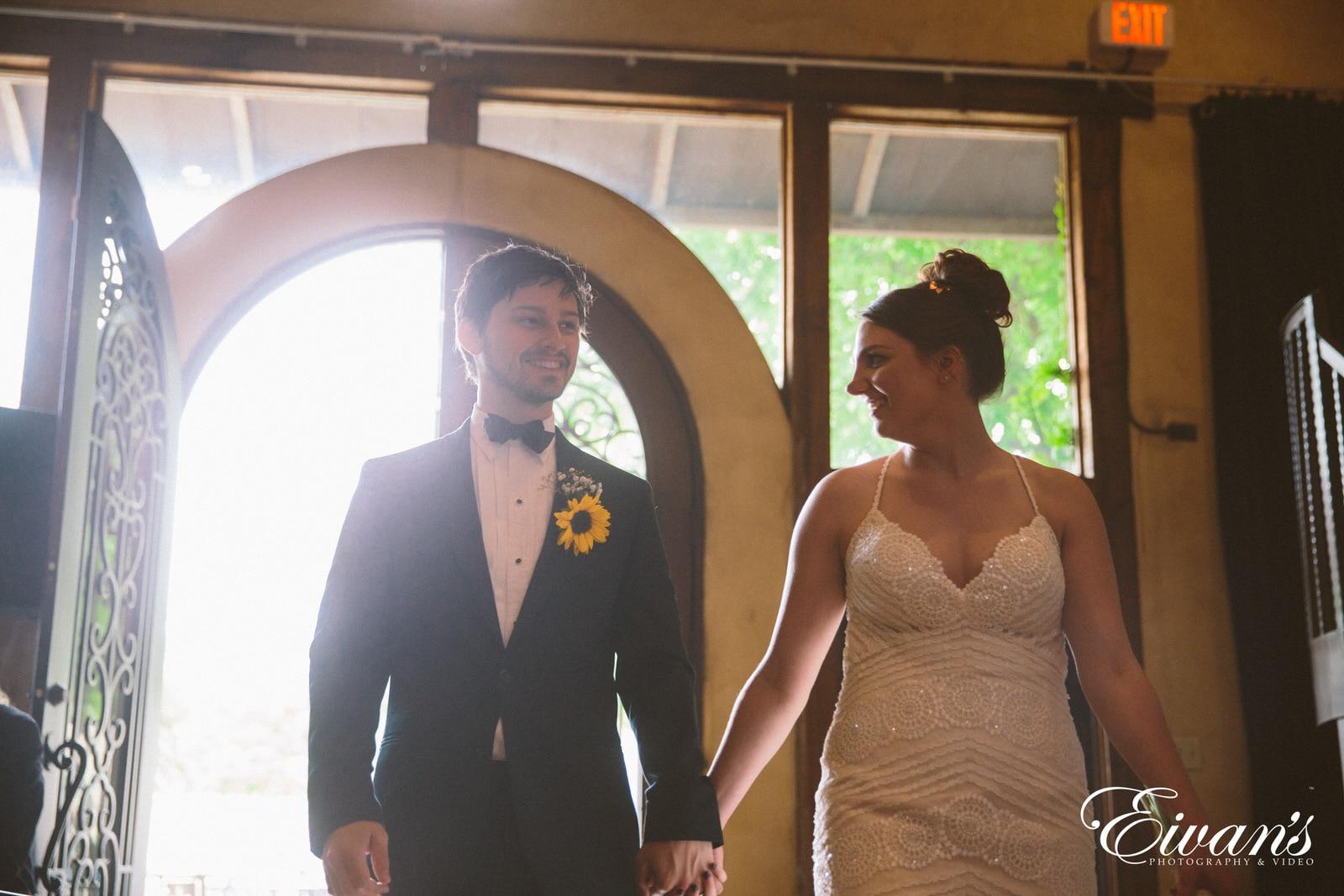man in black suit standing beside woman in brown sleeveless dress
