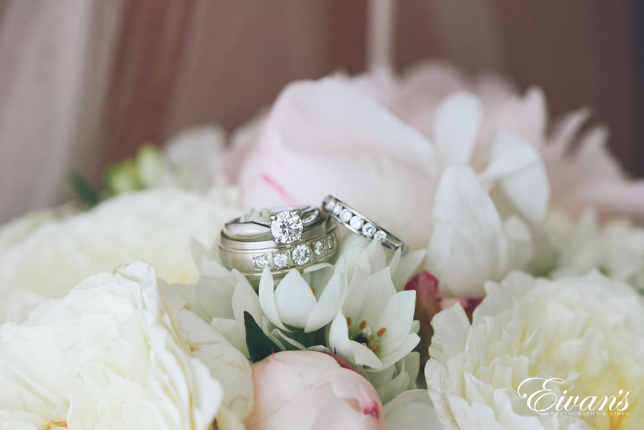 silver diamond ring on white flower petals