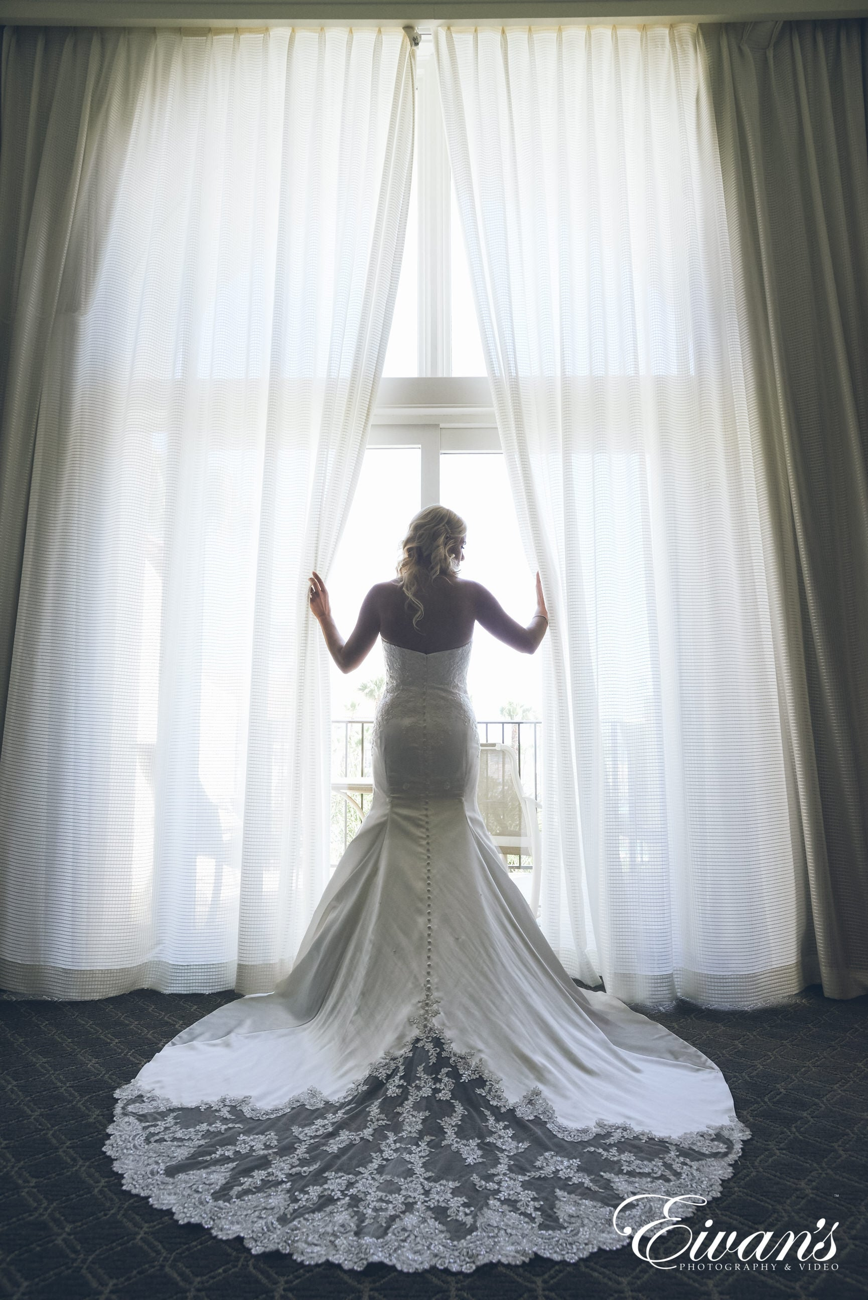woman in white wedding dress standing on white bed