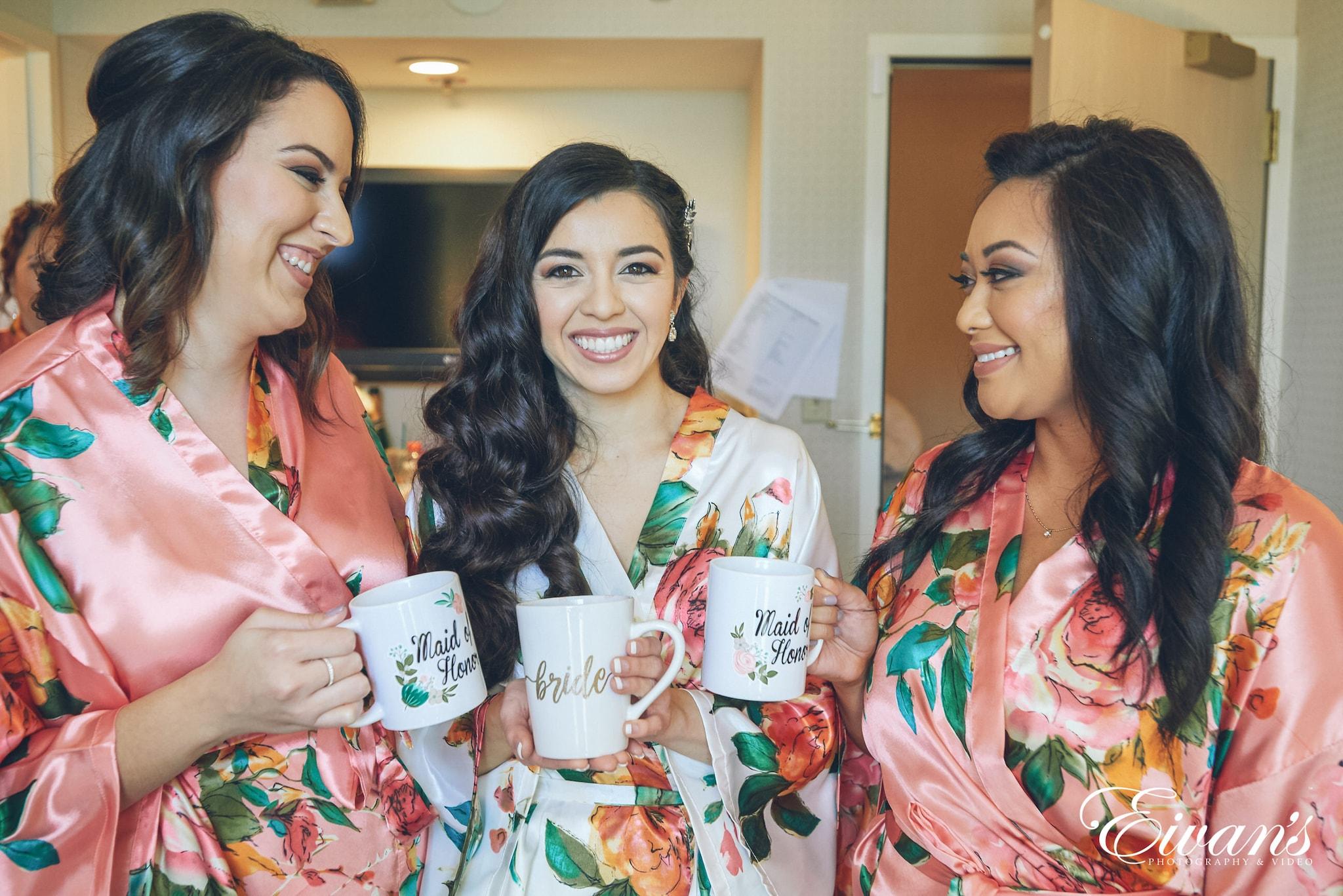 three women wearing floral robes holding mugs
