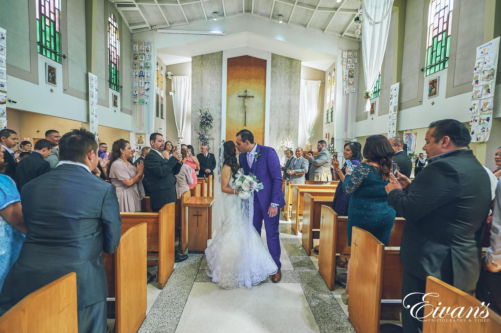 man and woman kissing down the aisle