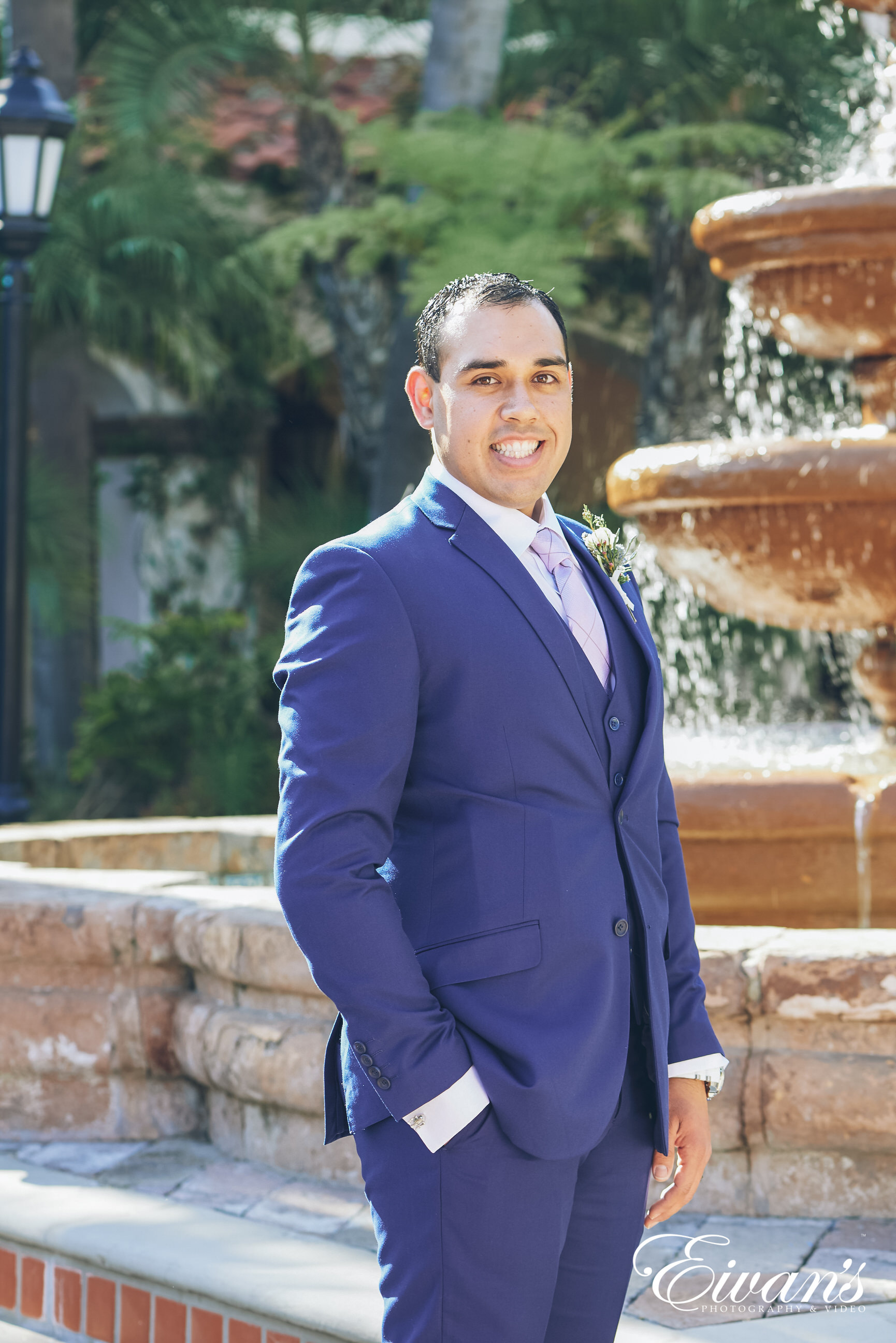 man wearing a dark blue suit posed in front of a fountain