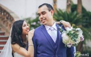 man in blue suit kissing woman in white wedding dress