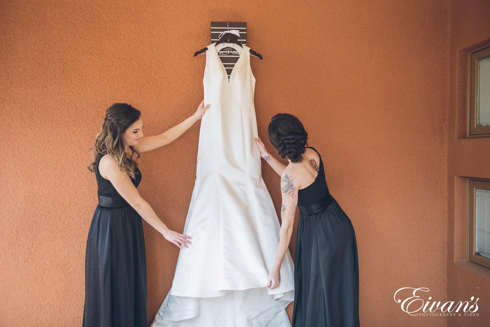 bridesmaids fixing a white wedding dress