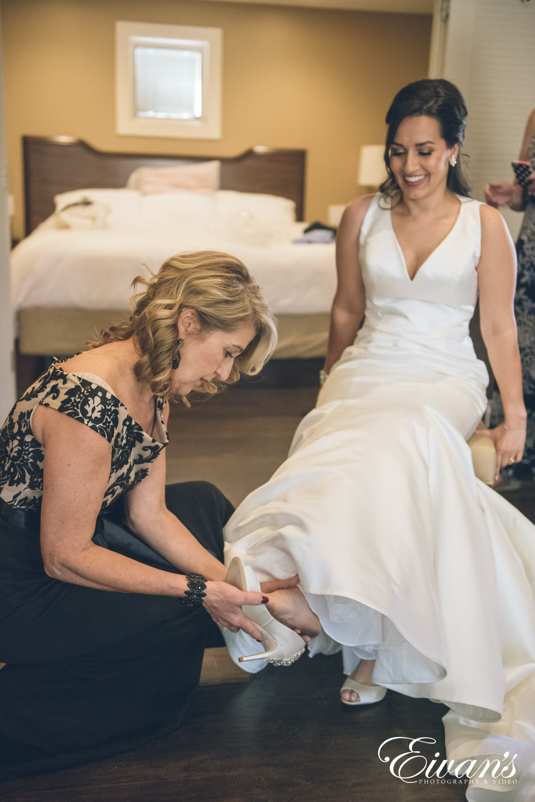 mother of the bride putting on brides shoes