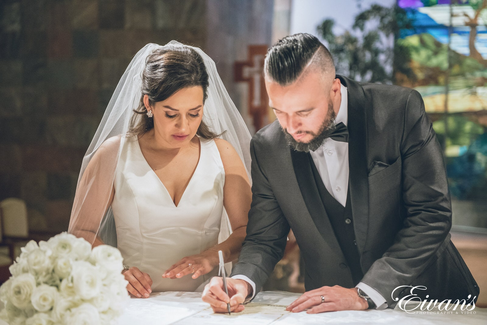 married man and woman signing their marriage license