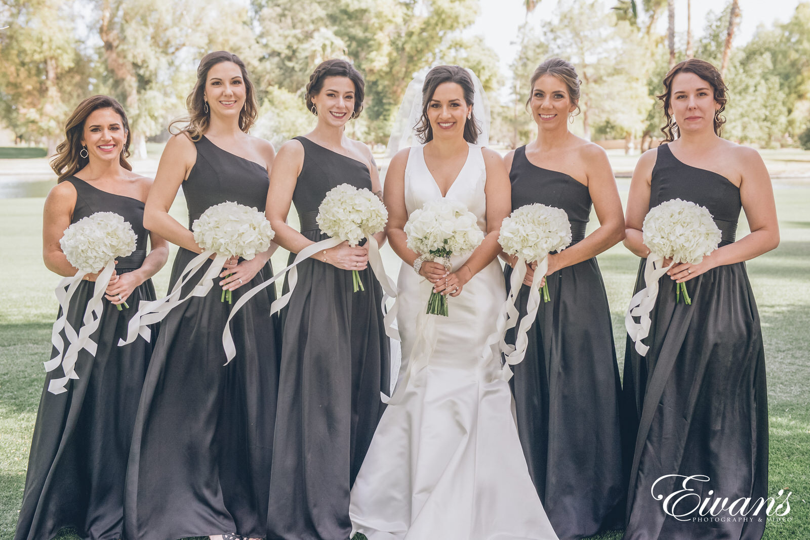 married woman standing next to bridesmaids wearing black dresses