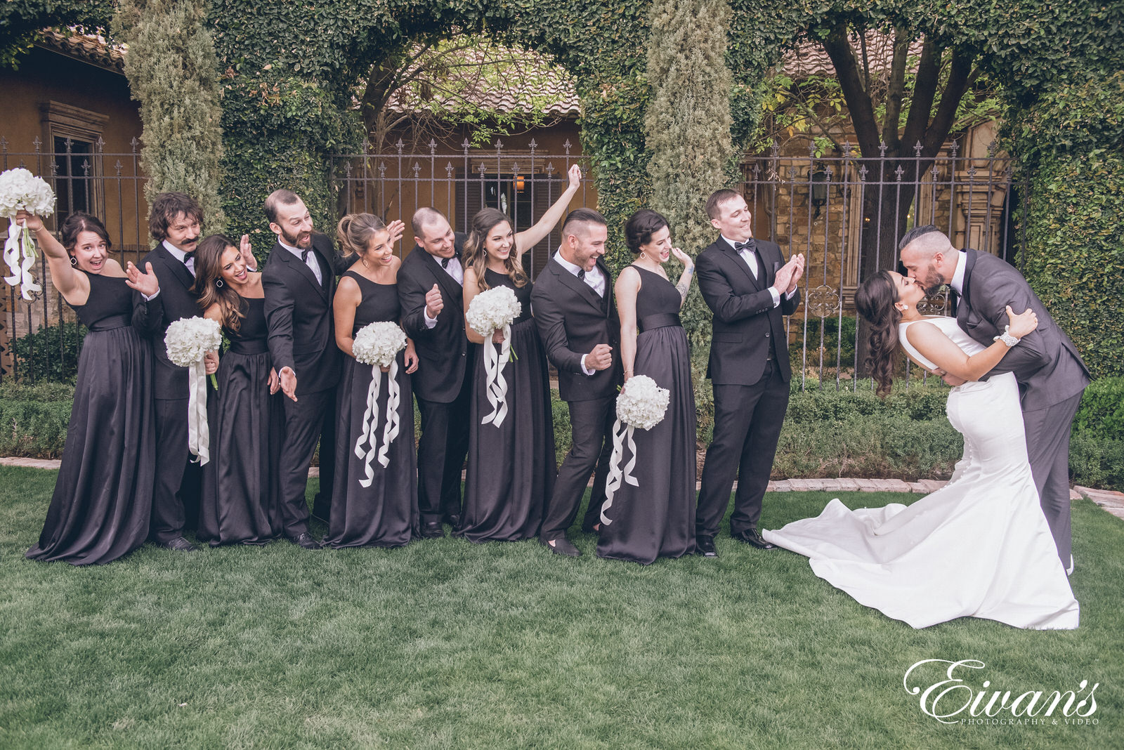 married man and woman kissing in front of a bridal party