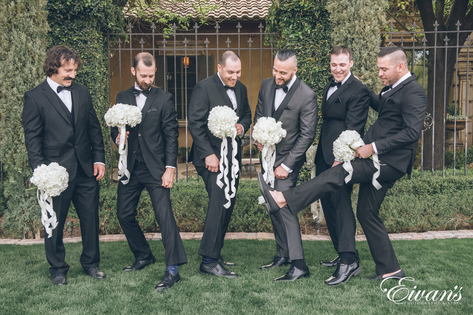 five men posed holding bouquets