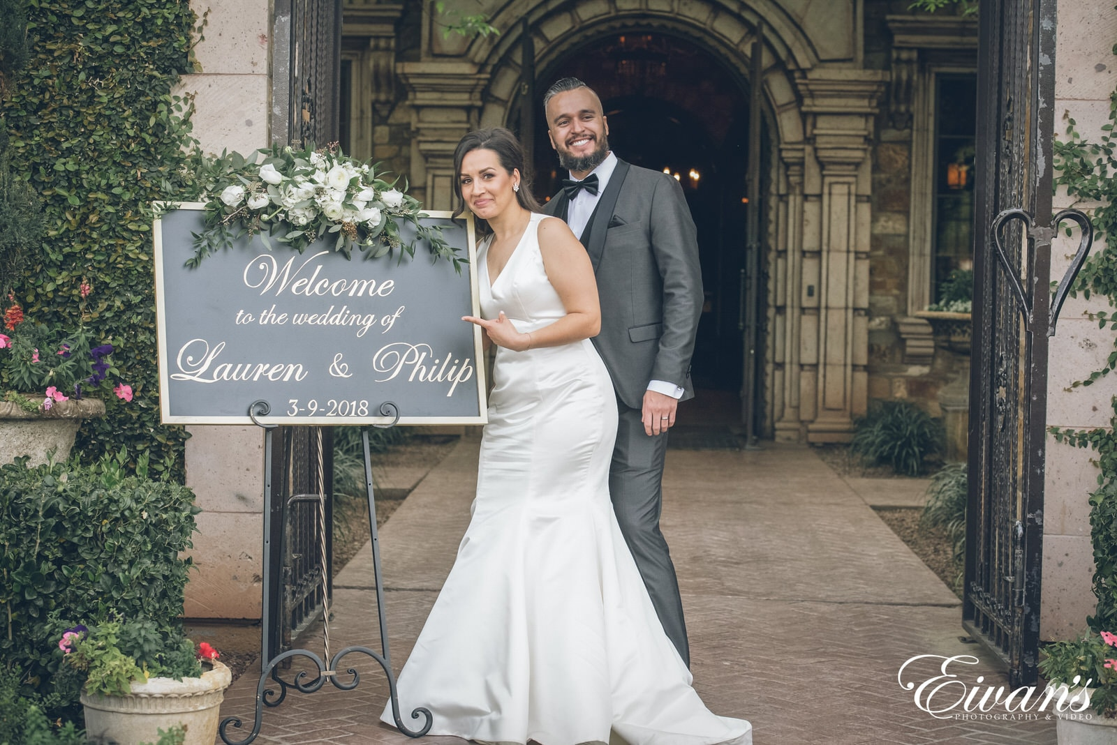 married man and woman standing by their welcome sign