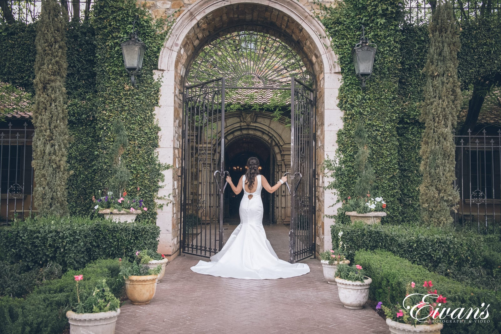 woman in a white dress entering and opening up the gates