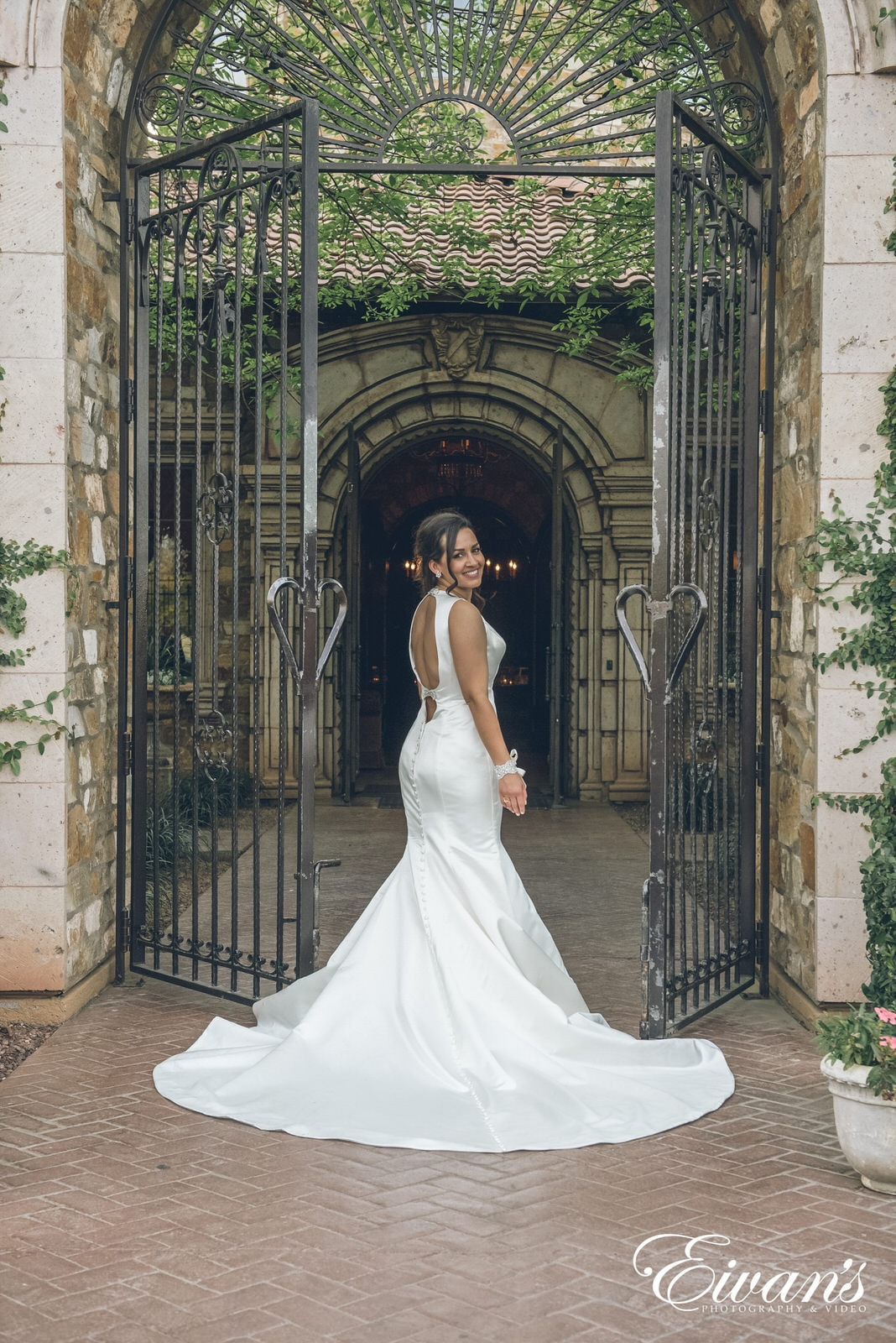 woman in a white dress standing in between open gates