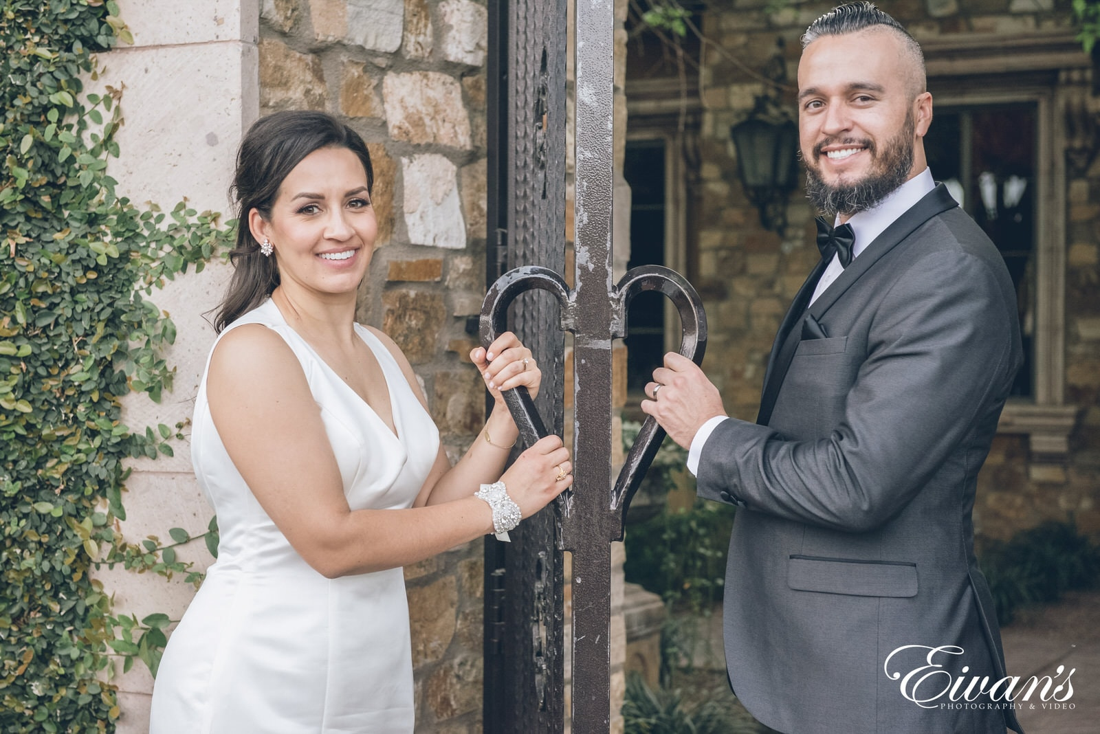 married man and woman standing next to a rusty gate