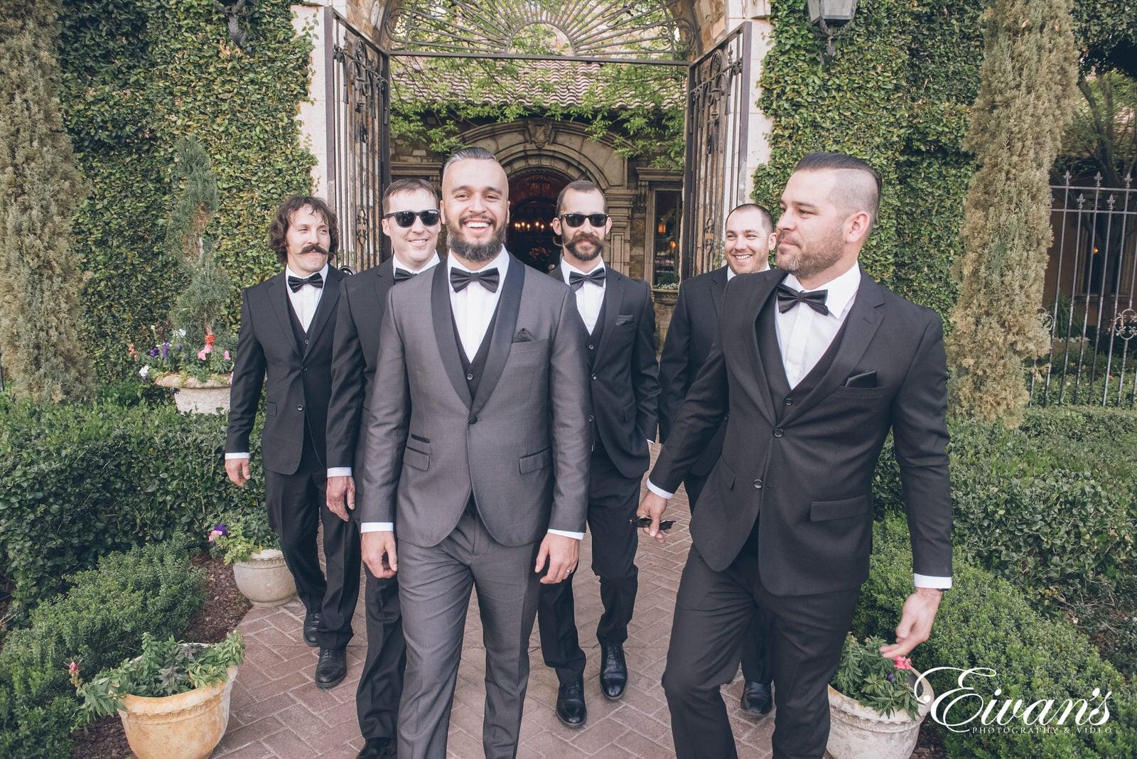 married man walking with his five groomsmen