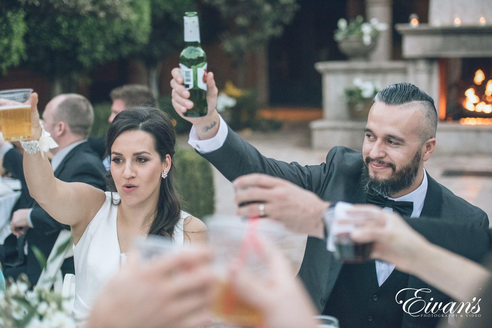 married man and woman holding their hands up with beer