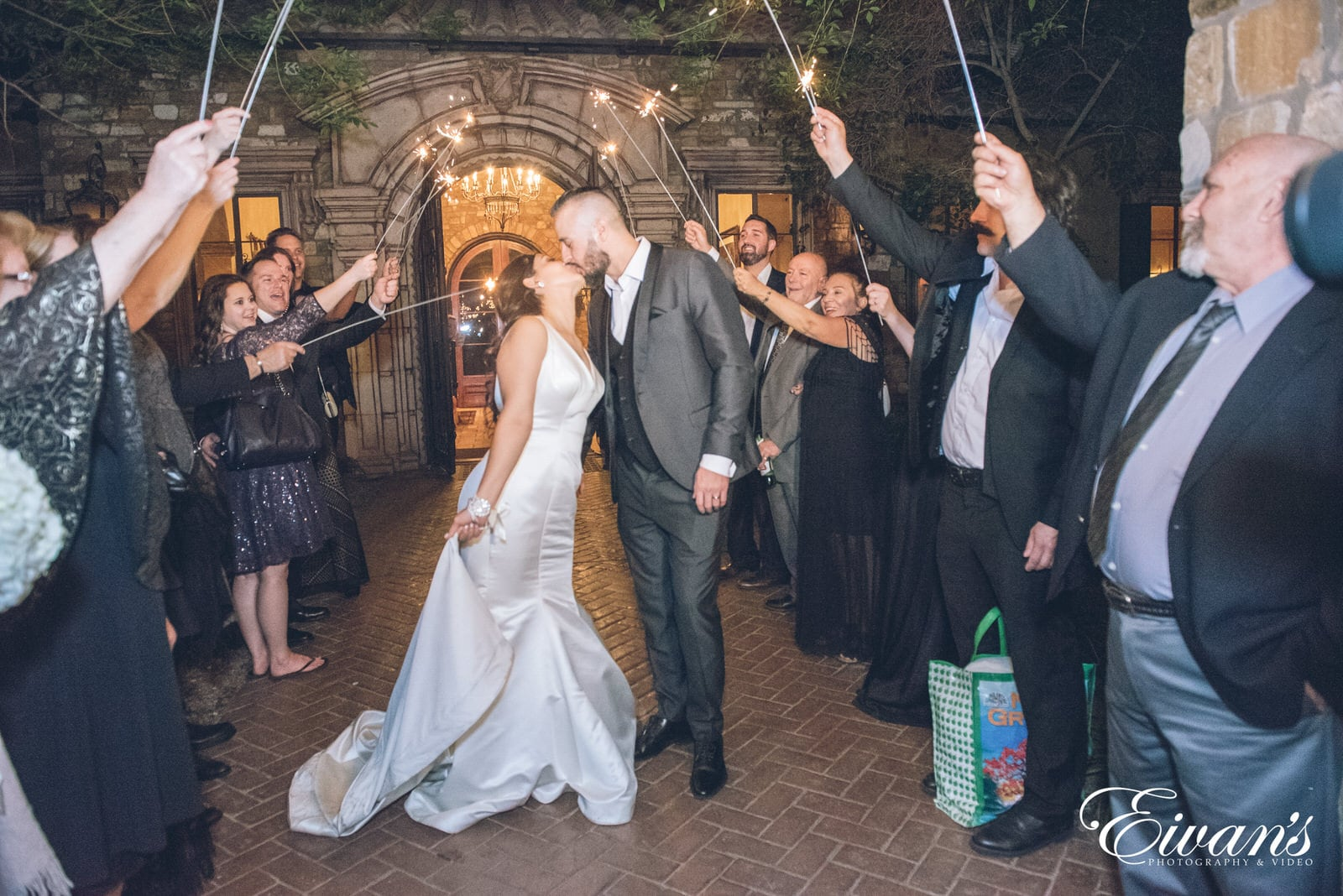 married man and woman kissing and guests are holding sprinklers