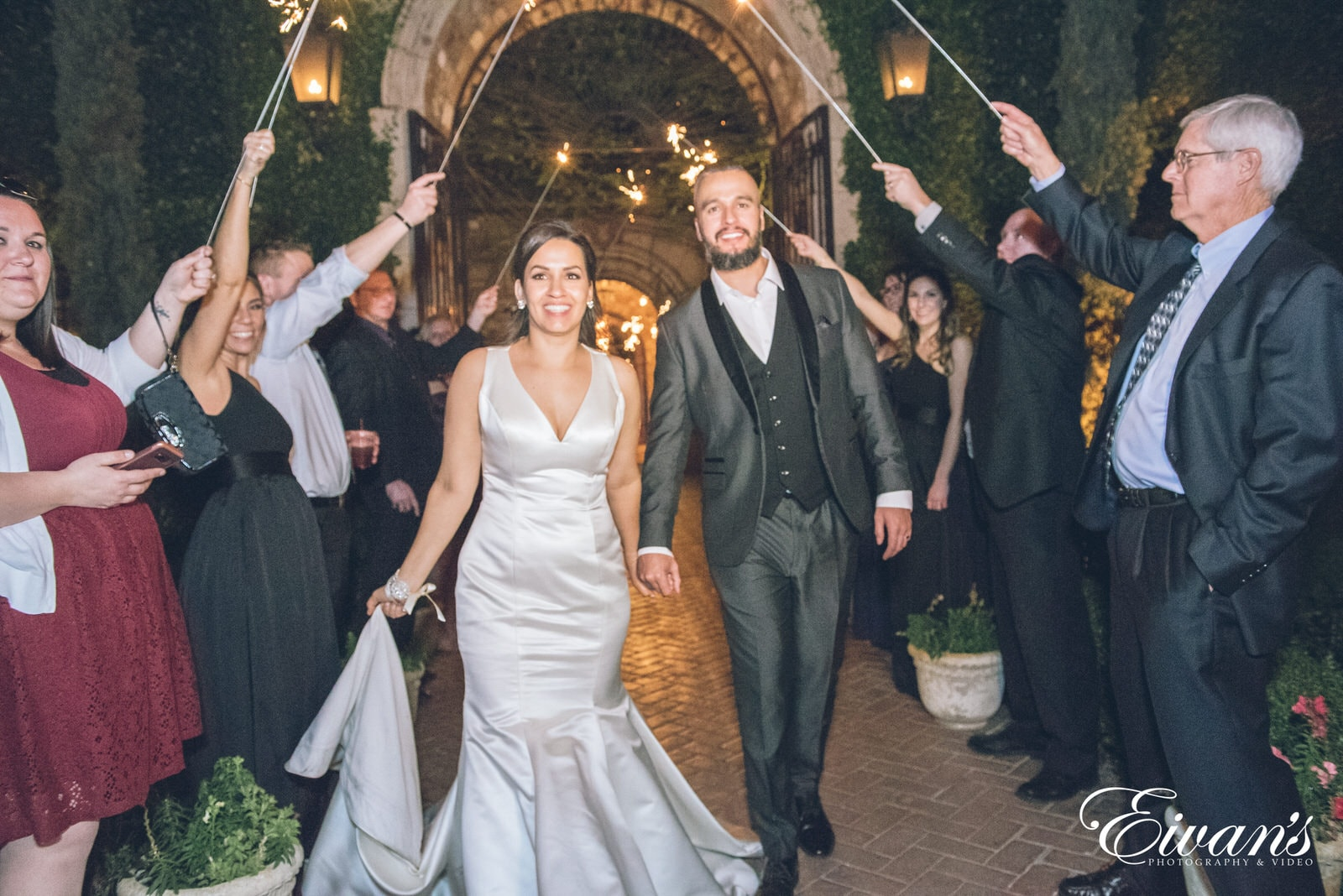 married man and woman walking through guests with sparklers
