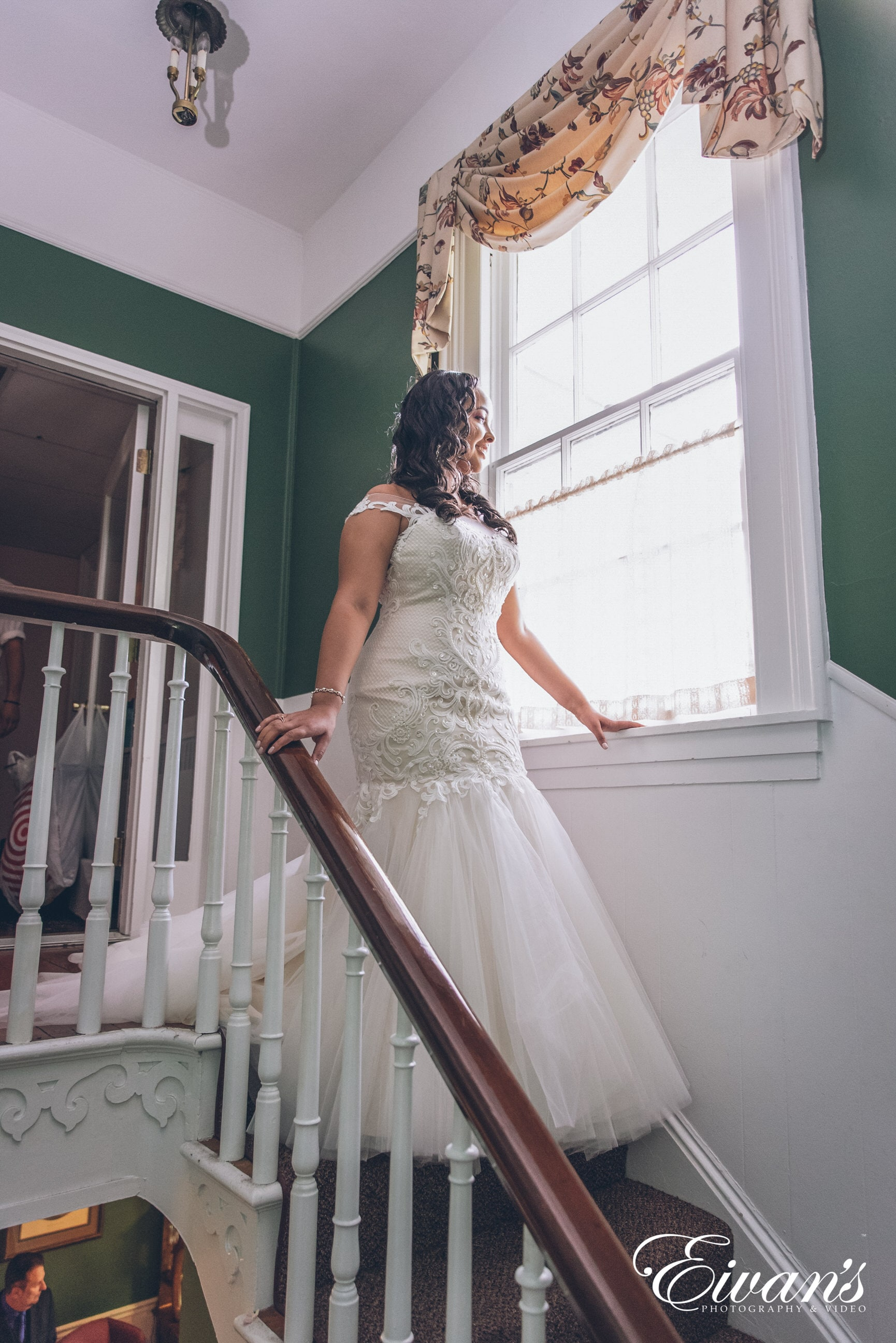 woman in white wedding dress standing on staircase