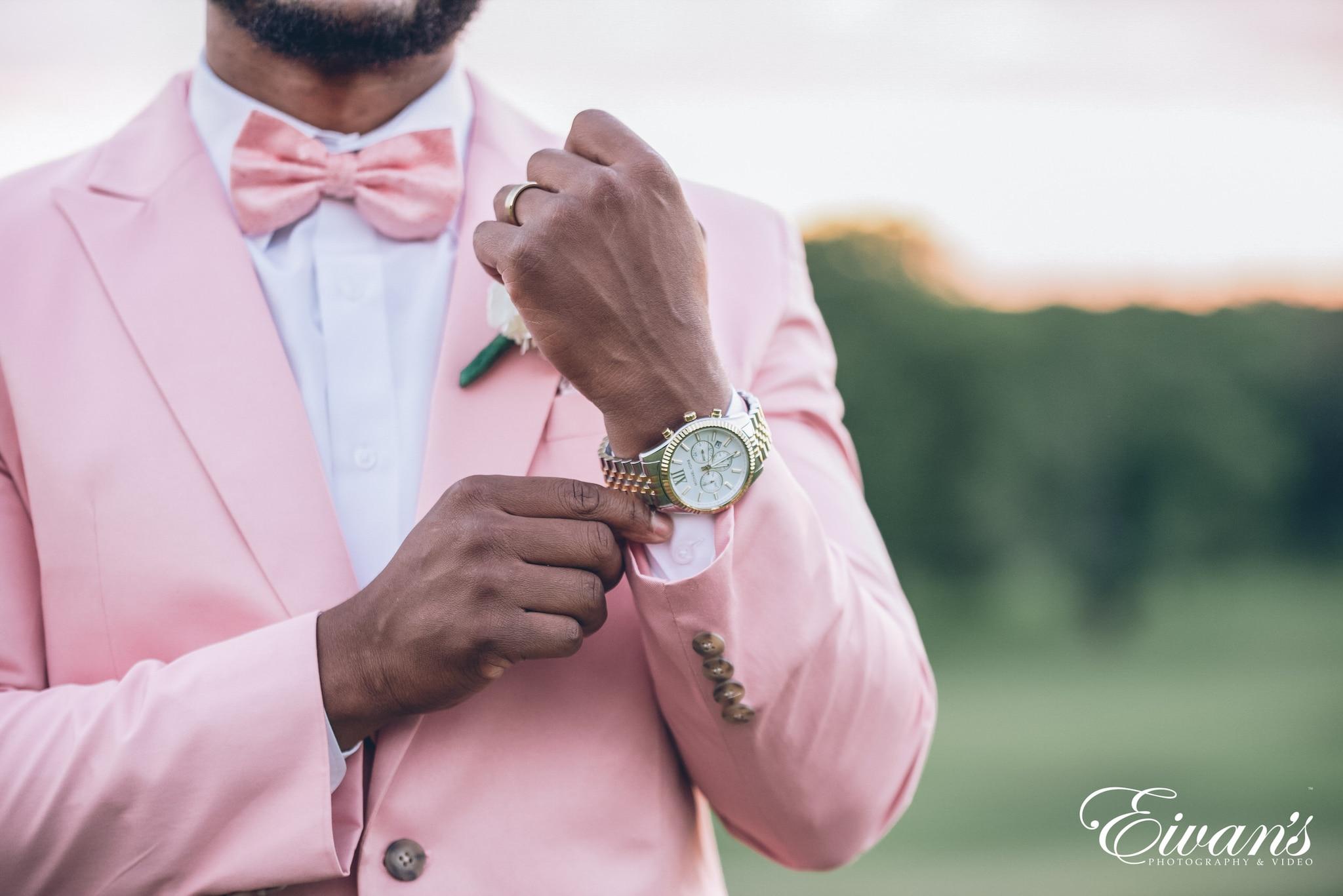 man in pink dress shirt wearing gold round analog watch