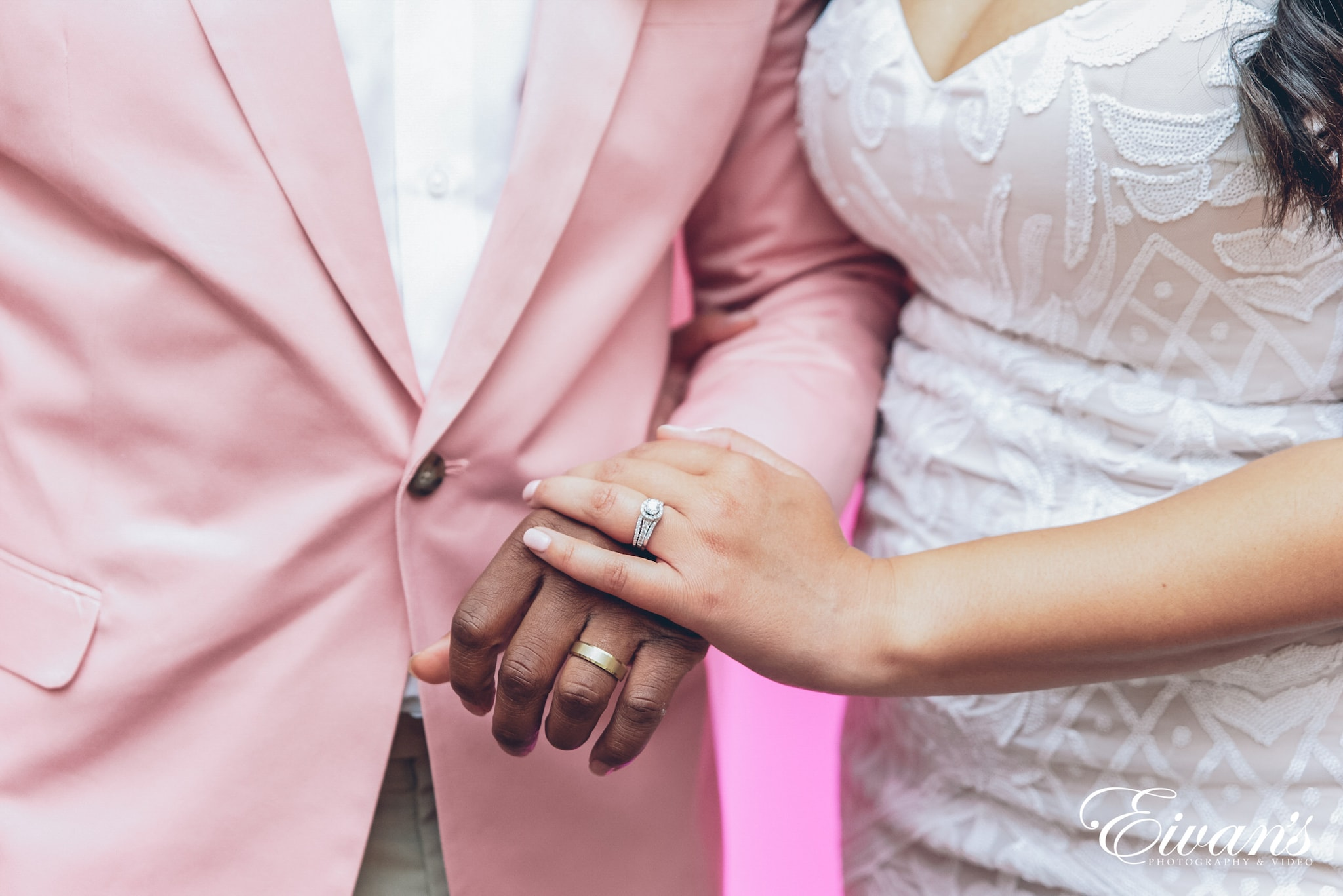 man and woman holding hands and showing off rings