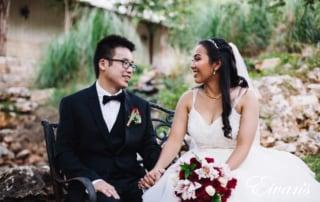 man in black suit jacket sitting beside woman in white wedding dress