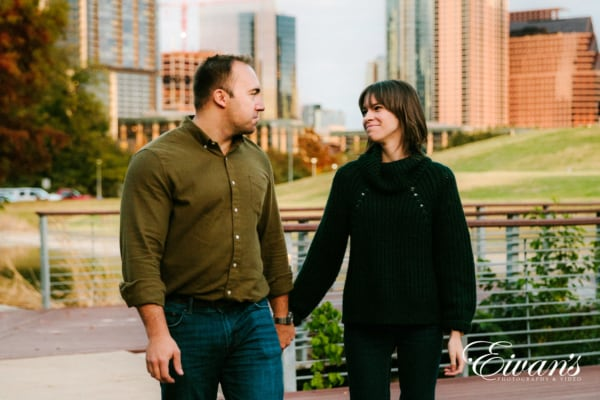classic pose of engagement couple walking in park