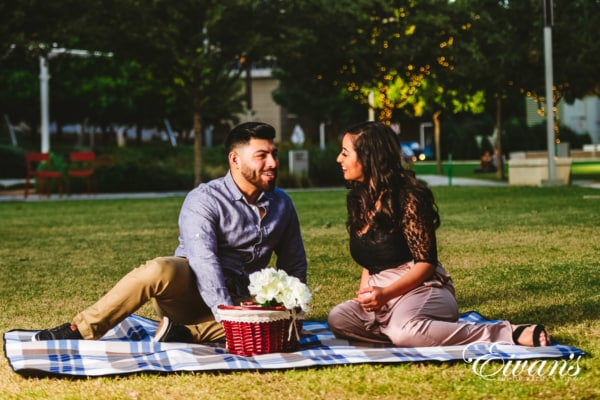 engagedcouple sitting in front of their university campus