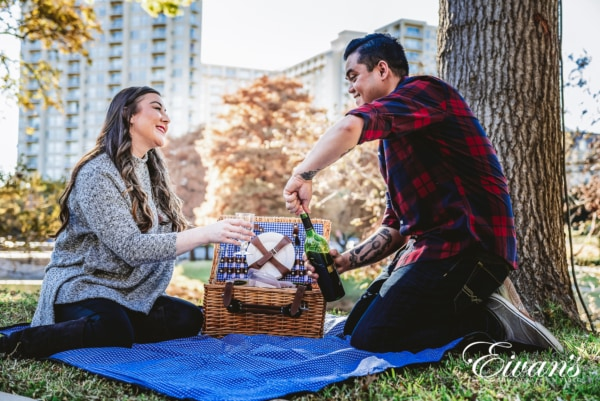 couple having a picnic at a state park while taking a candid engagement photo