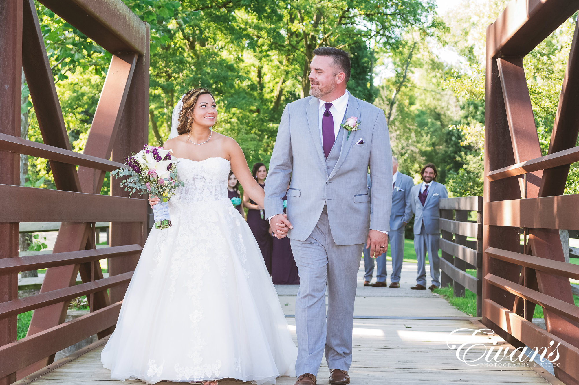 man in gray suit and woman in white wedding dress walking on sidewalk during daytime
