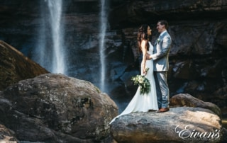 man and woman standing on rock near waterfalls during daytime