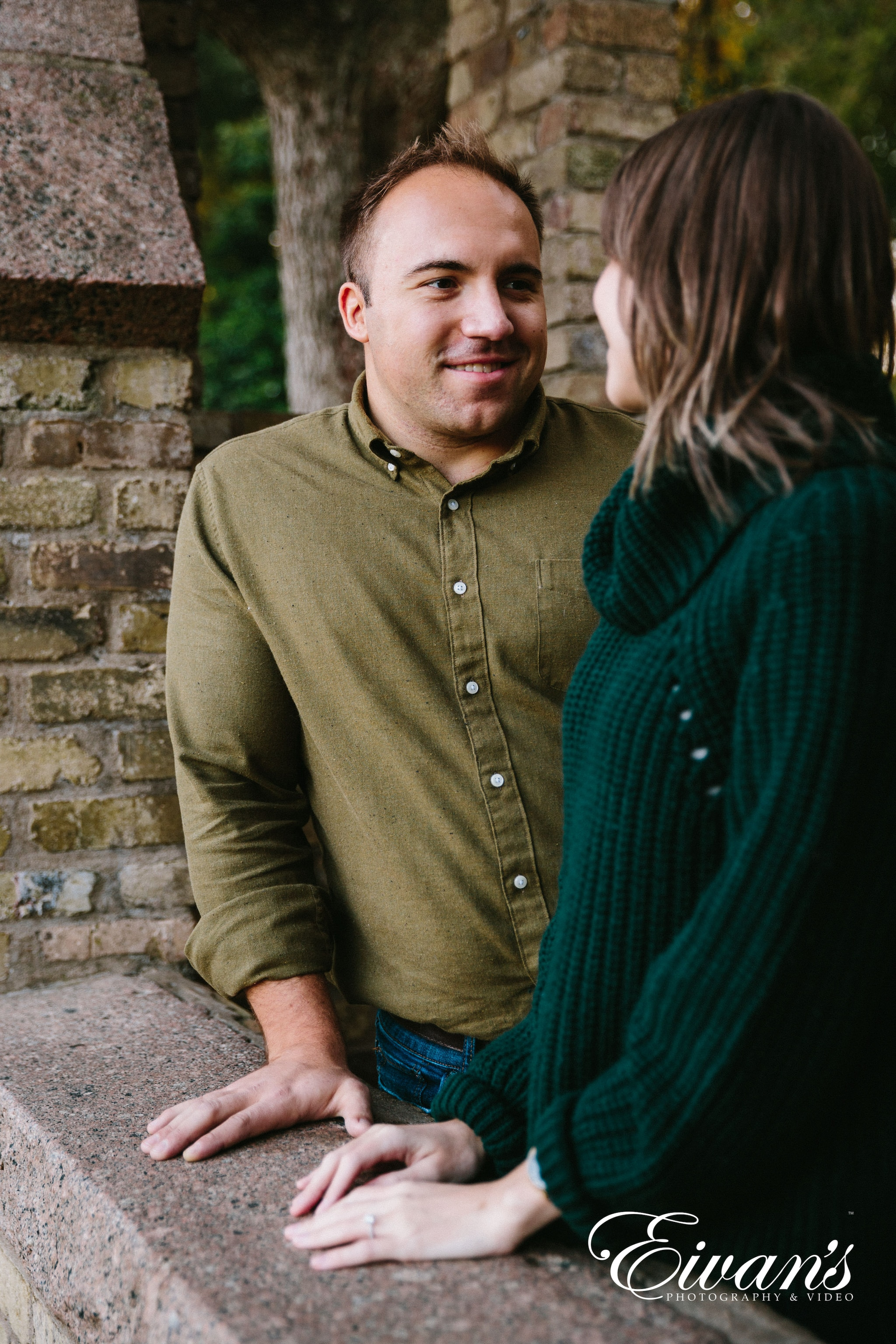 engaged couple wearing green pose for a photoshoot