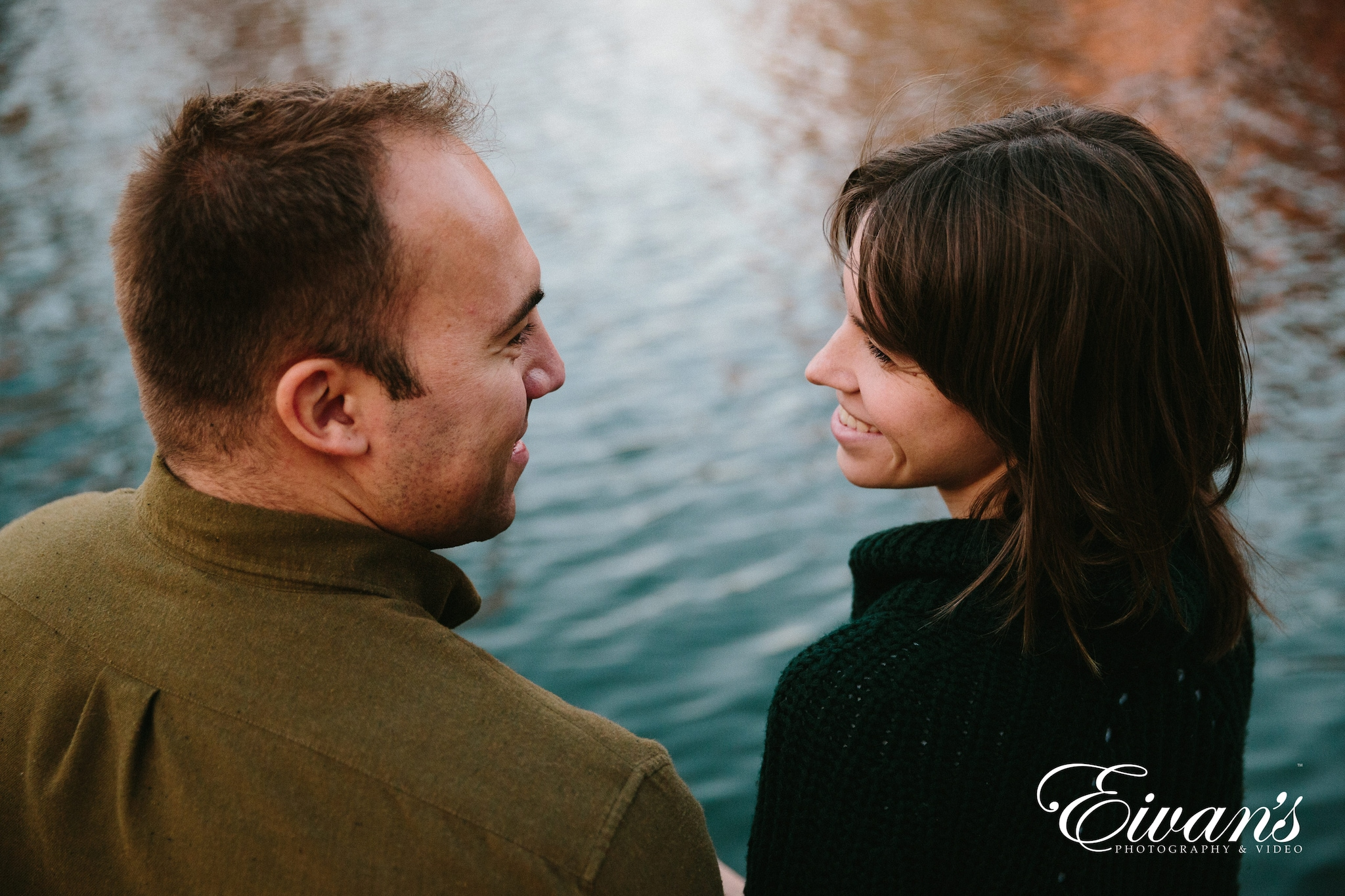 two engaged couple looking at each other in front of a lake