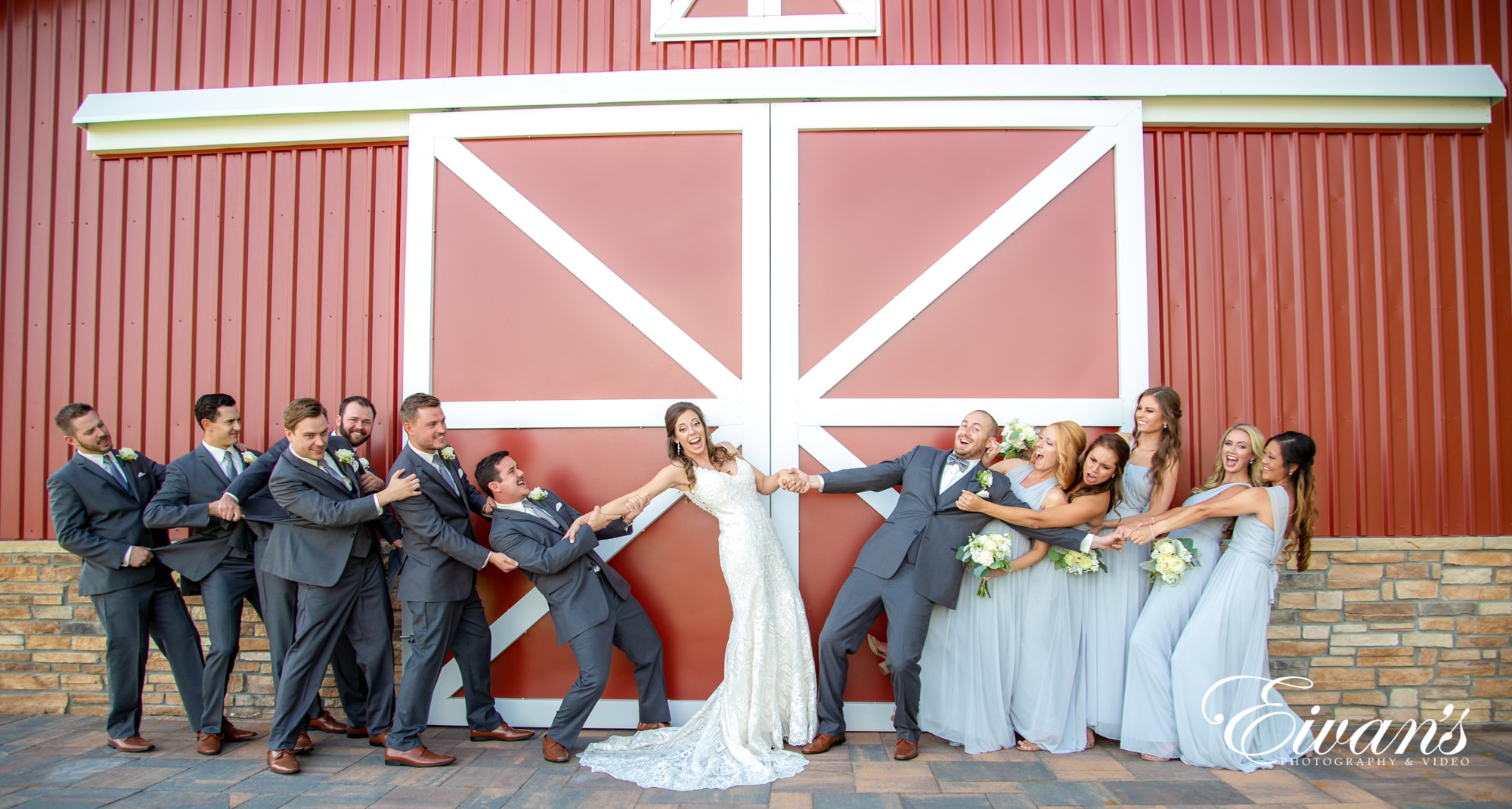Bridal party posed in front of big red barn doors