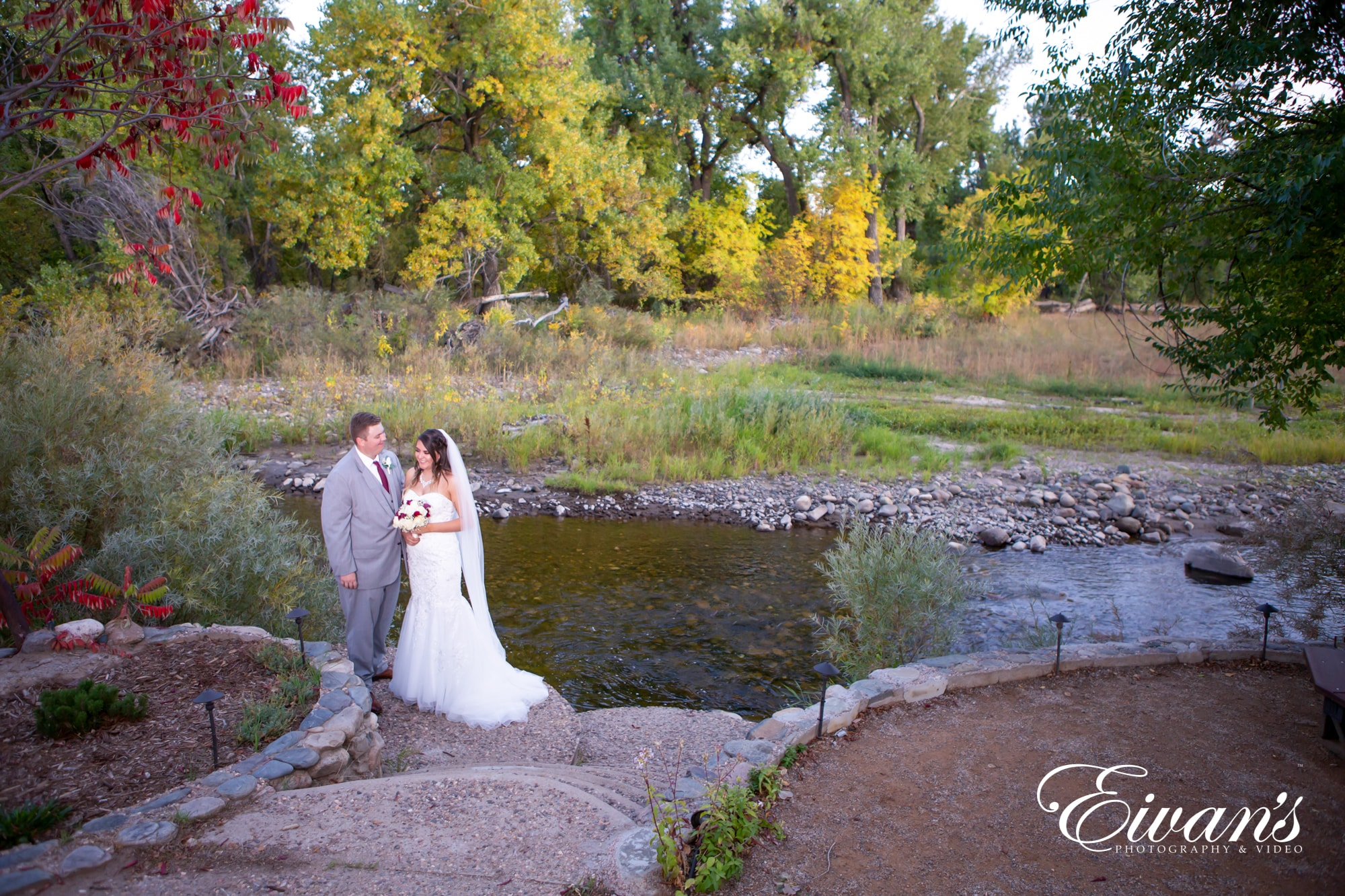 married couple posed in front of a pond