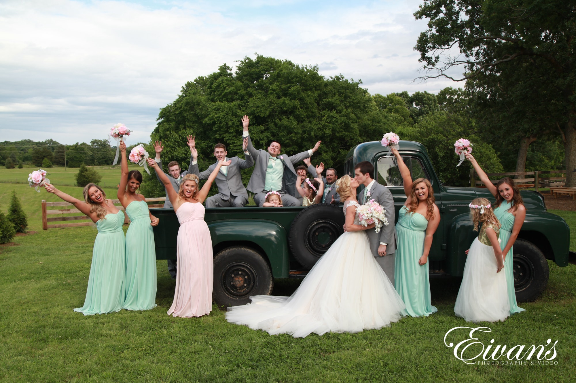 bridal party posed in front of a green pickup truck