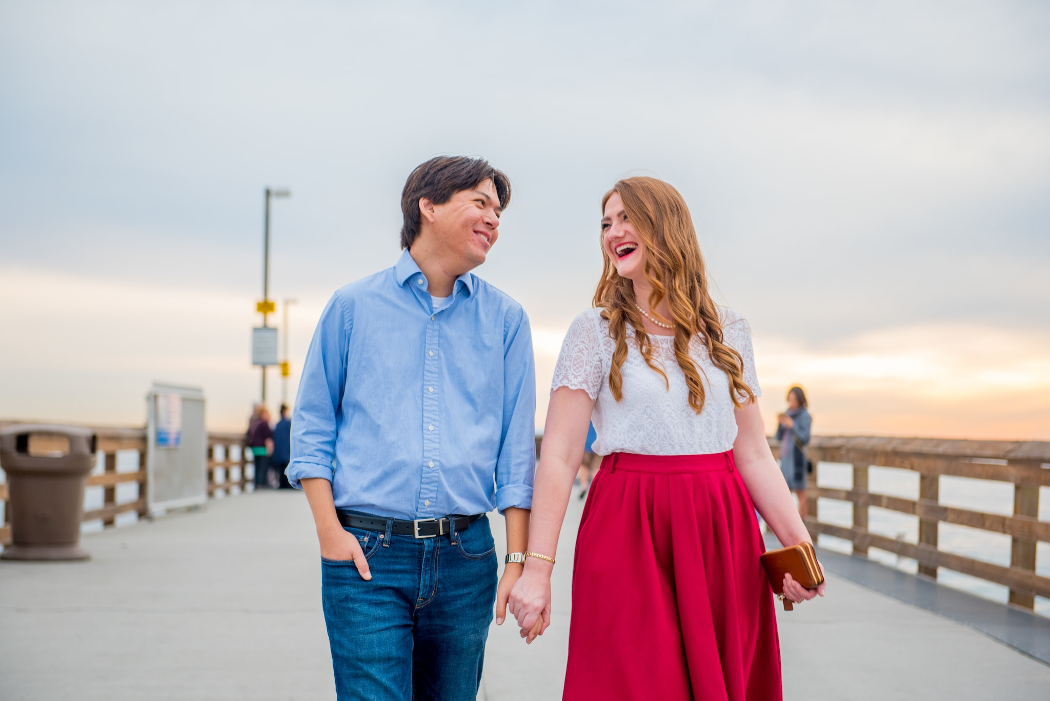 Man wearing blue shirt and jeans holding hand with woman wearing white shirt and pink skirt while walking on the boardwalk