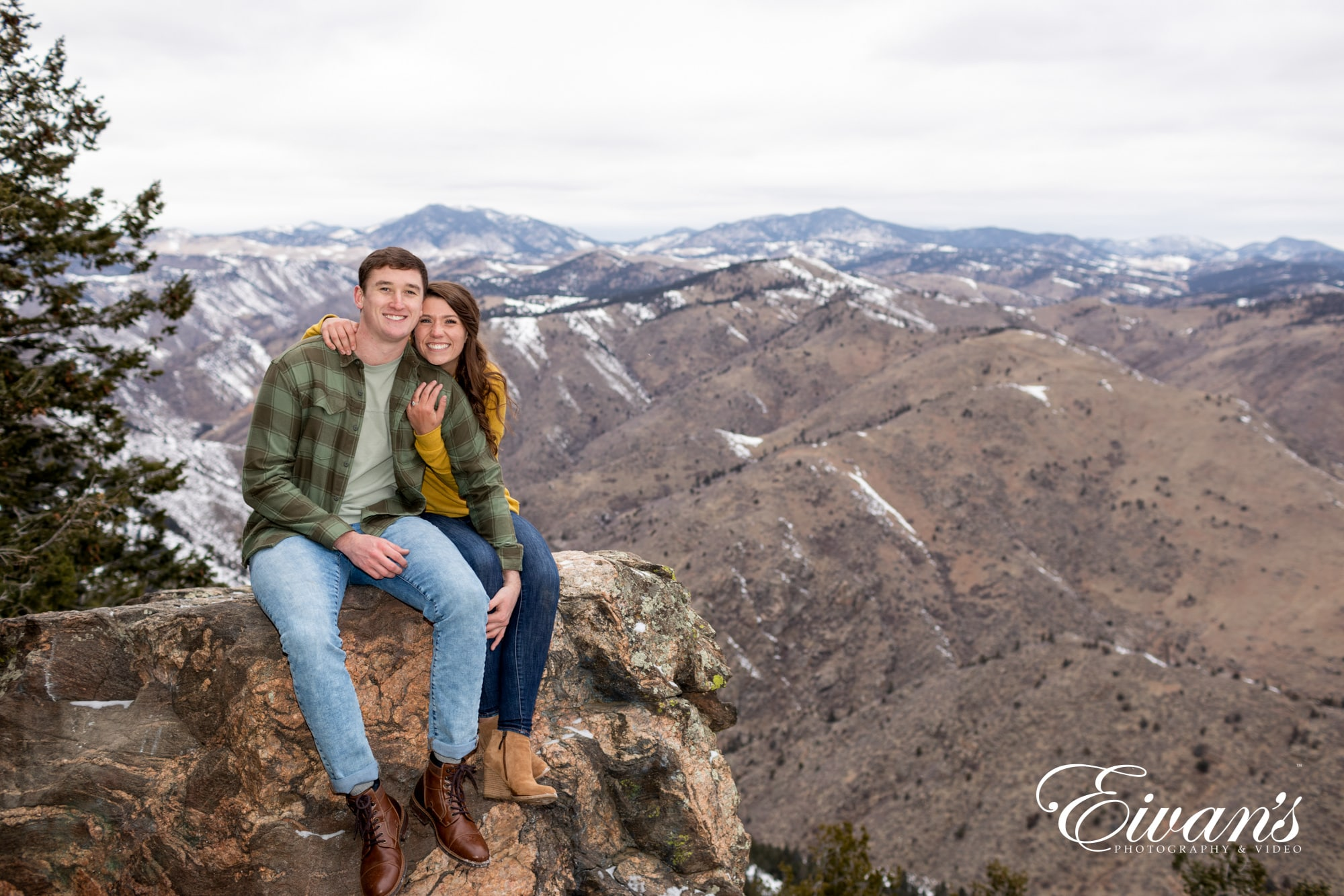 engaged couple posed on a cliff