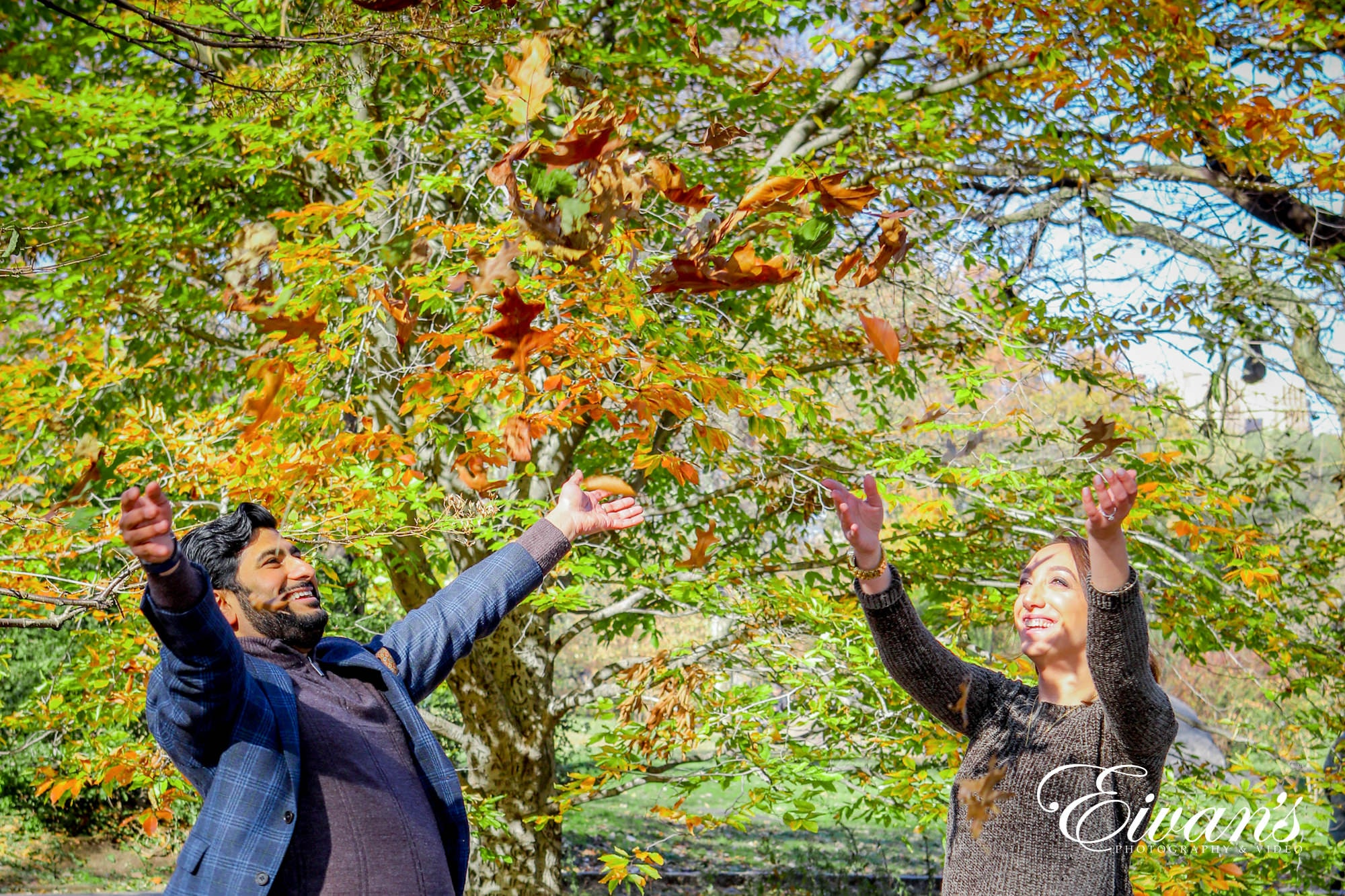engaged couple throwing autumn leaves in the air