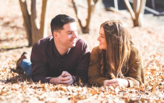 engaged couple posed on the ground surrounded by autumn leaves