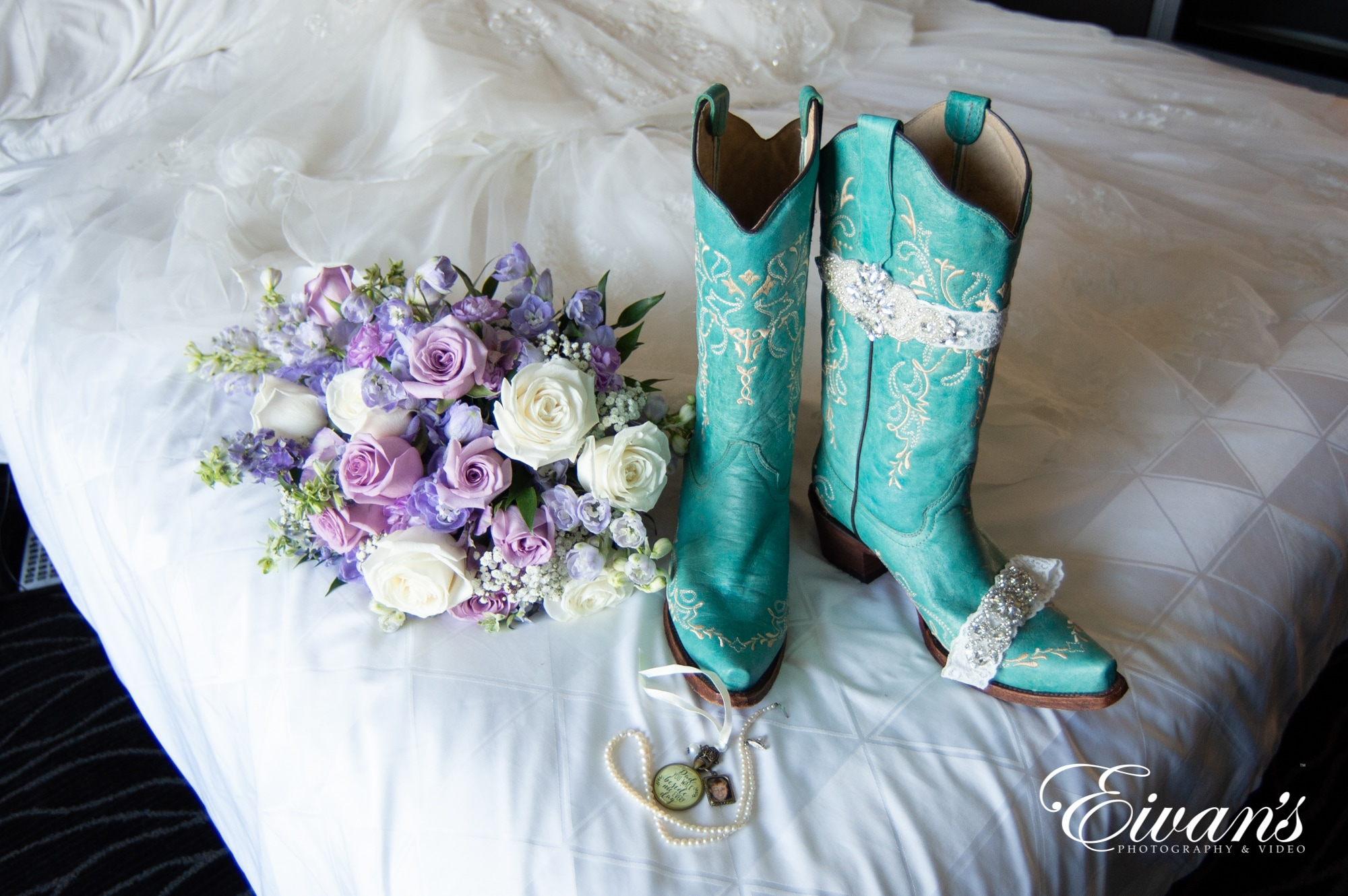 image of boots and a bouquet on a bed