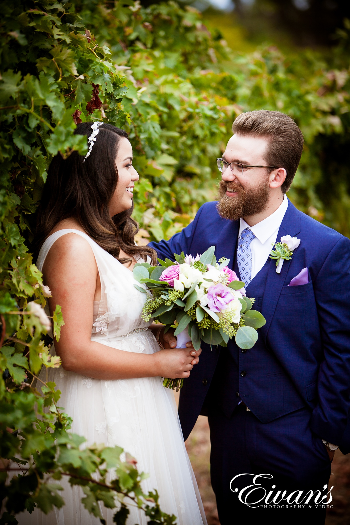 image of a bride and groom standing in front of a wall of greenery