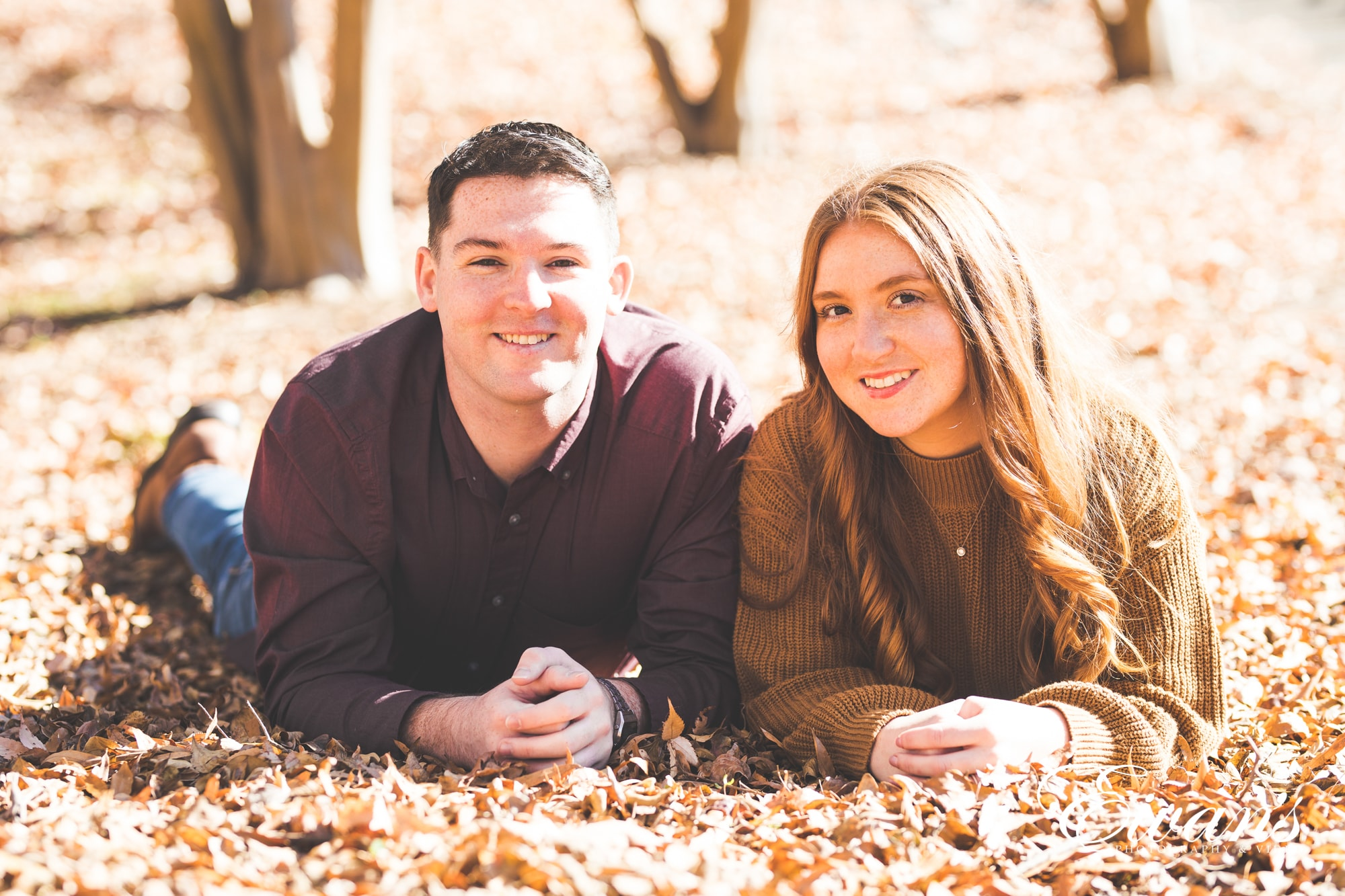 couple posed on the group surrounded by autumn leaves