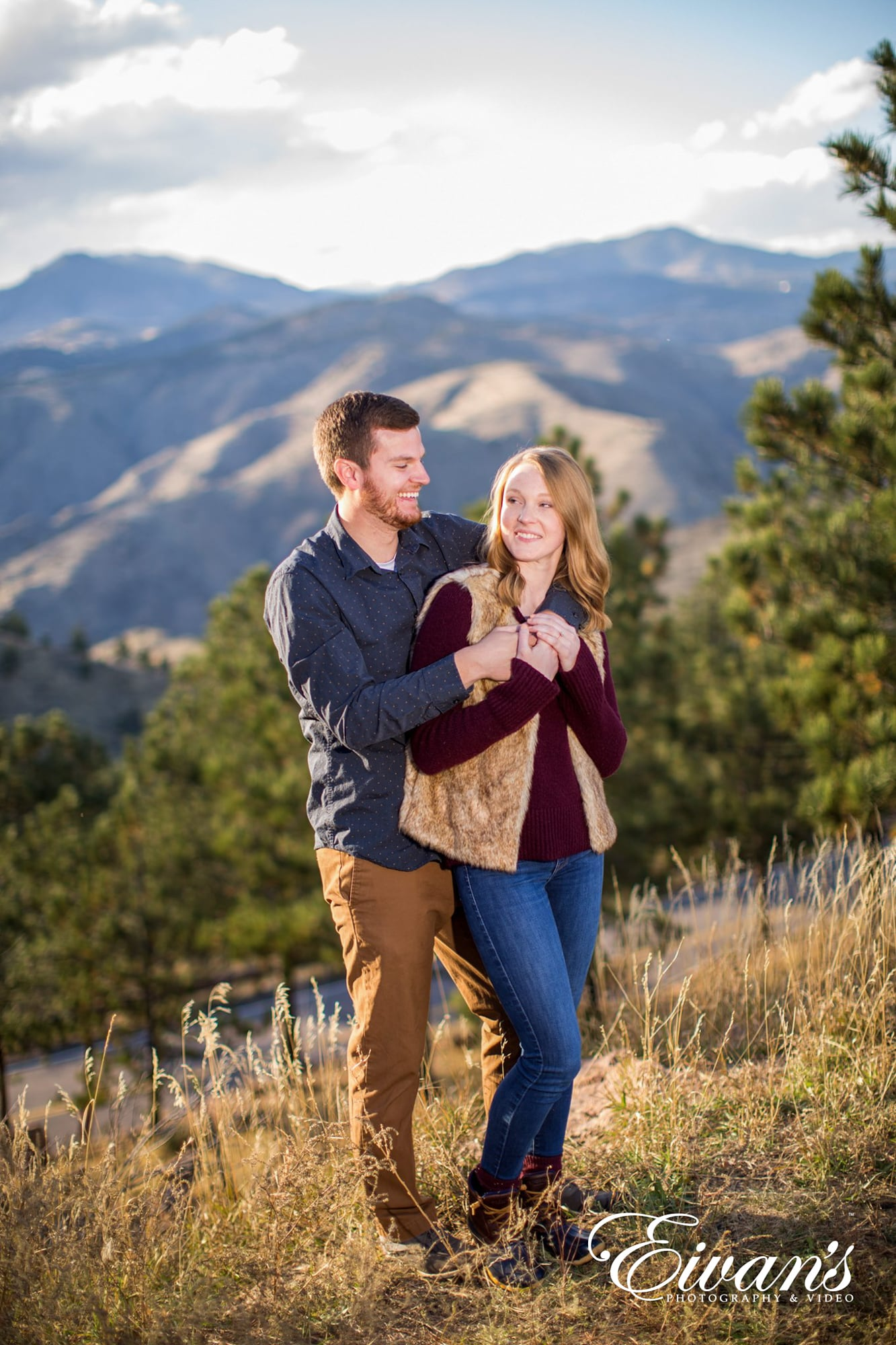 couple posed in front of rocky mountains in the fall