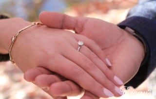 engaged man holding his fiancees hand