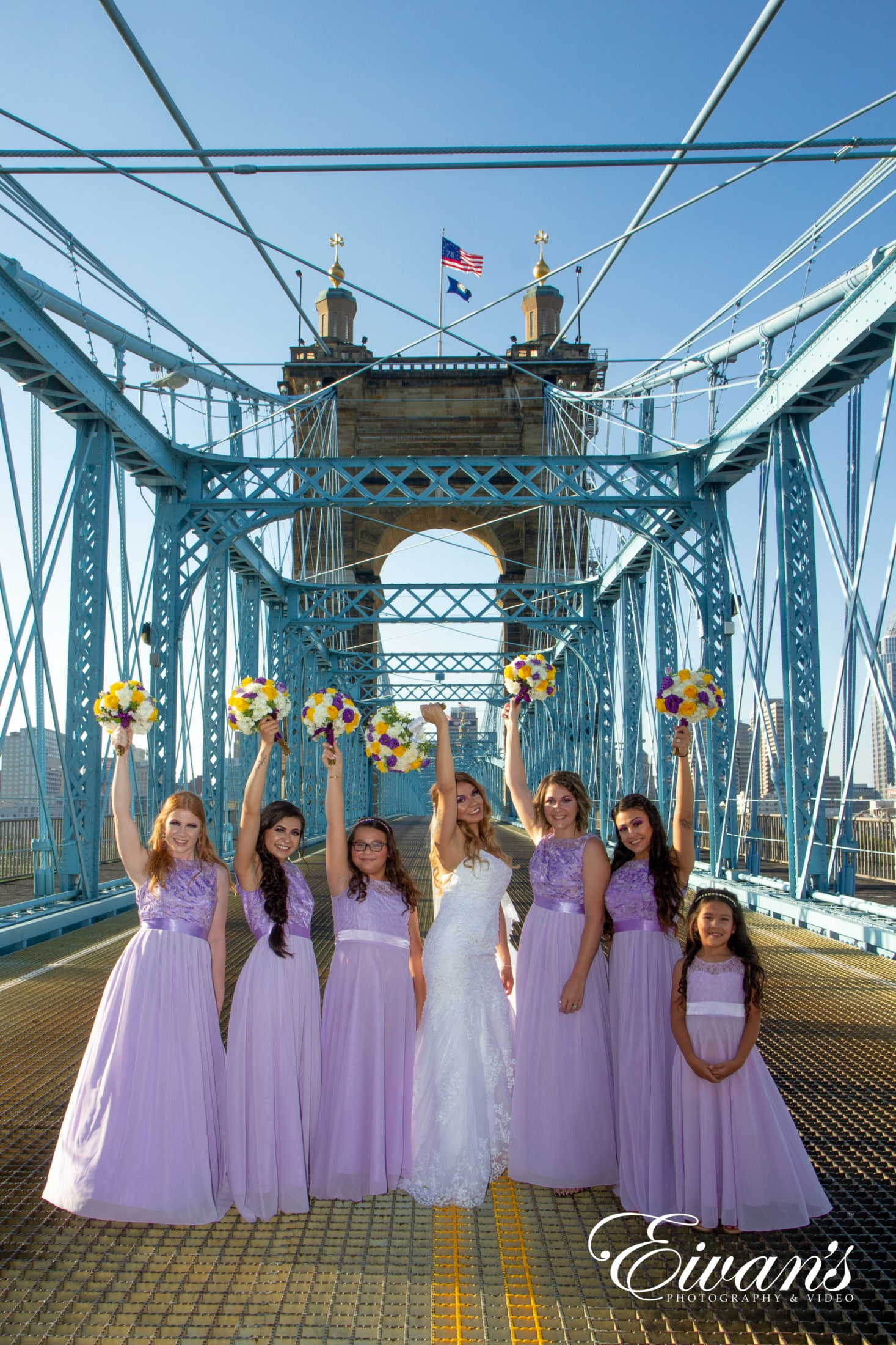 an image of a bride and her bridesmaids on the bridge