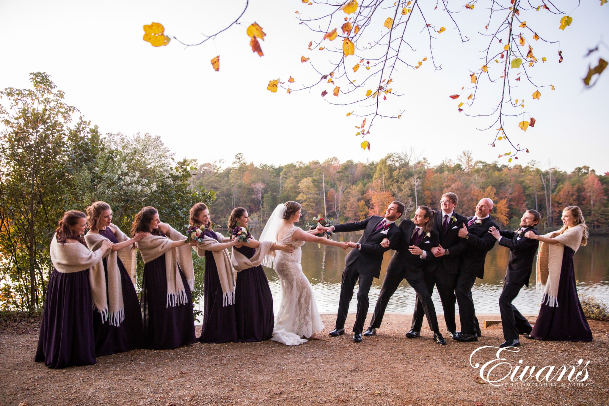 image of wedding party playing tug of war with the newlyweds