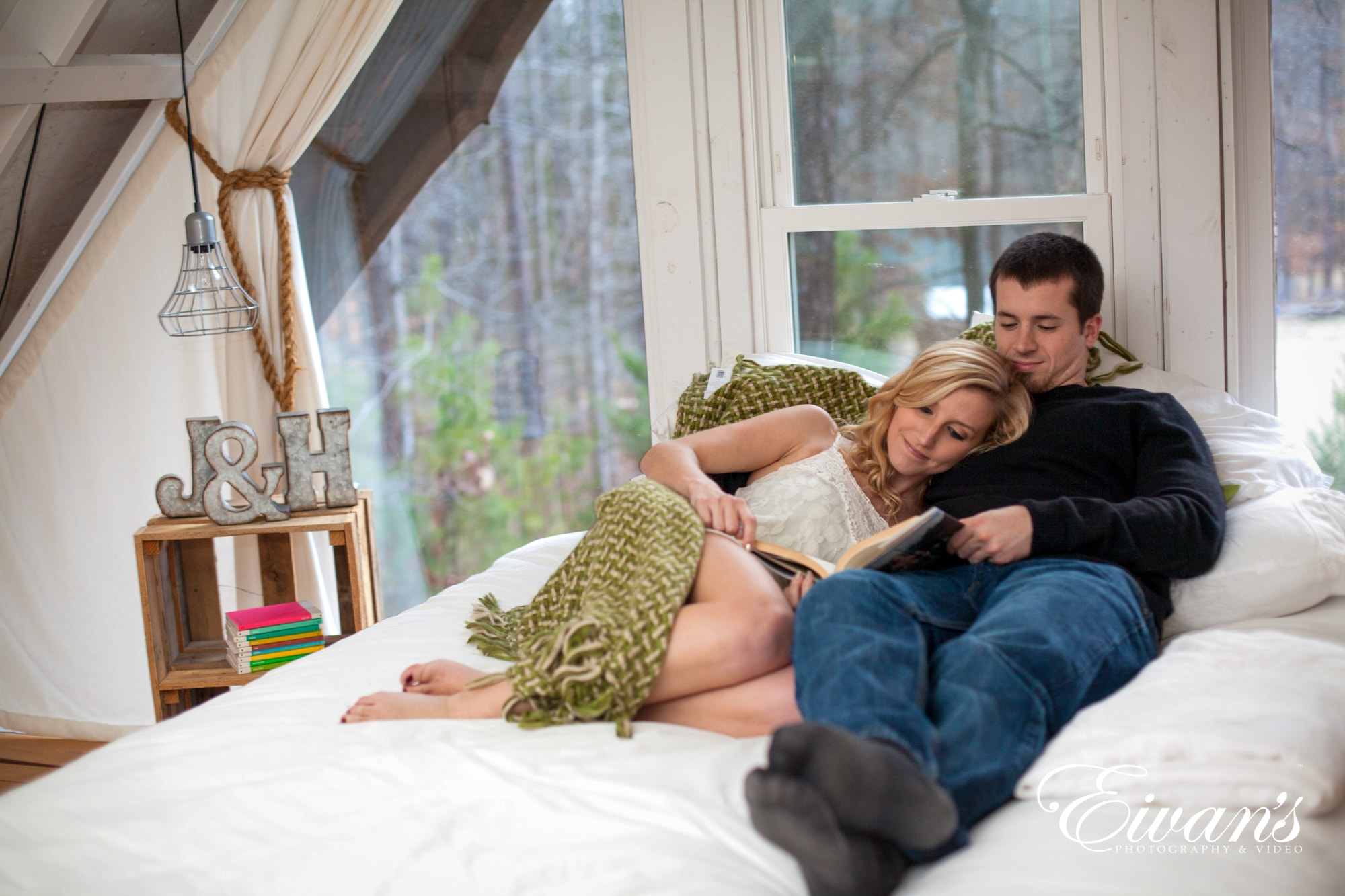 Image of an engaged man and woman laying on their bed at home