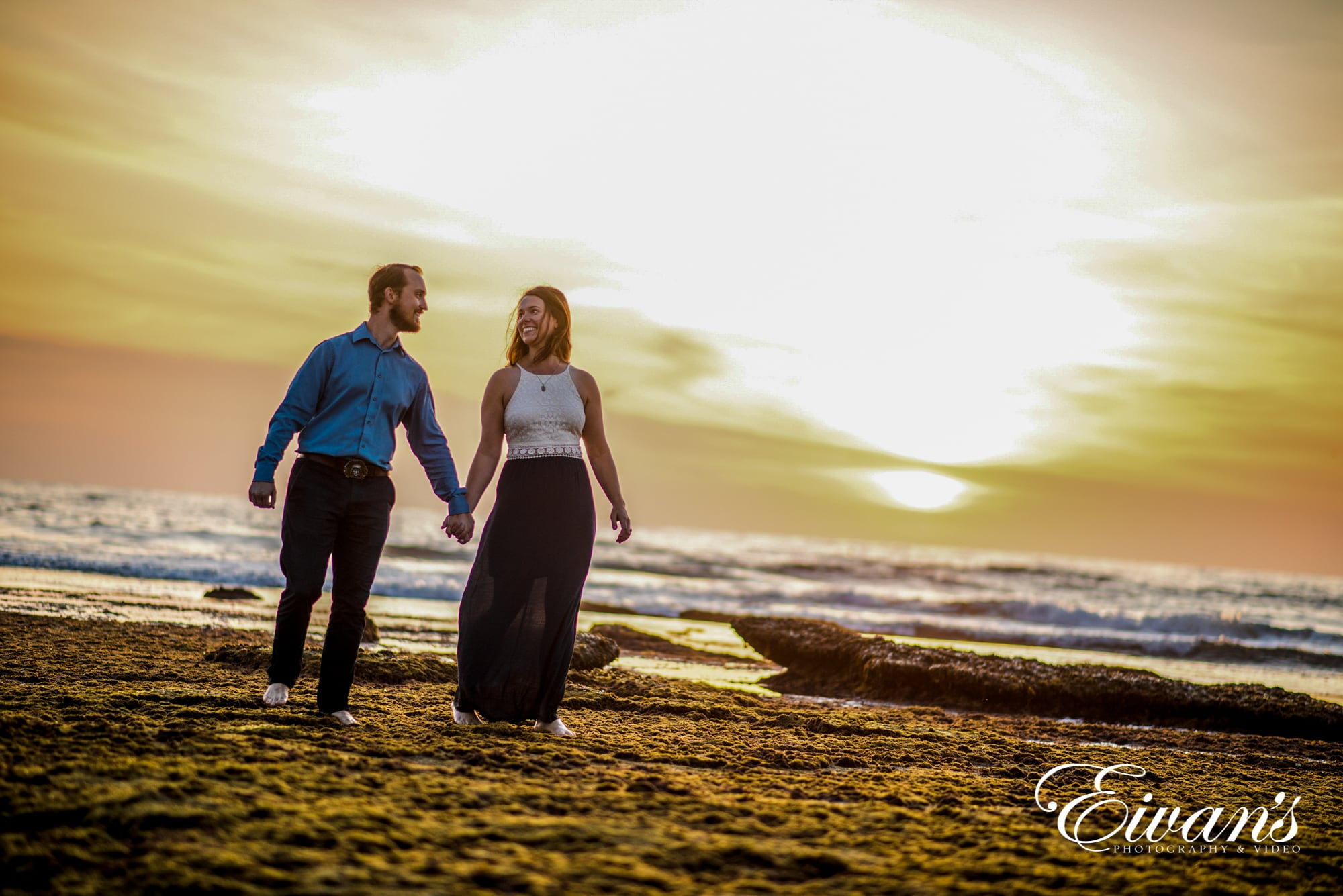 Image of a couple walking on the beach during sunset