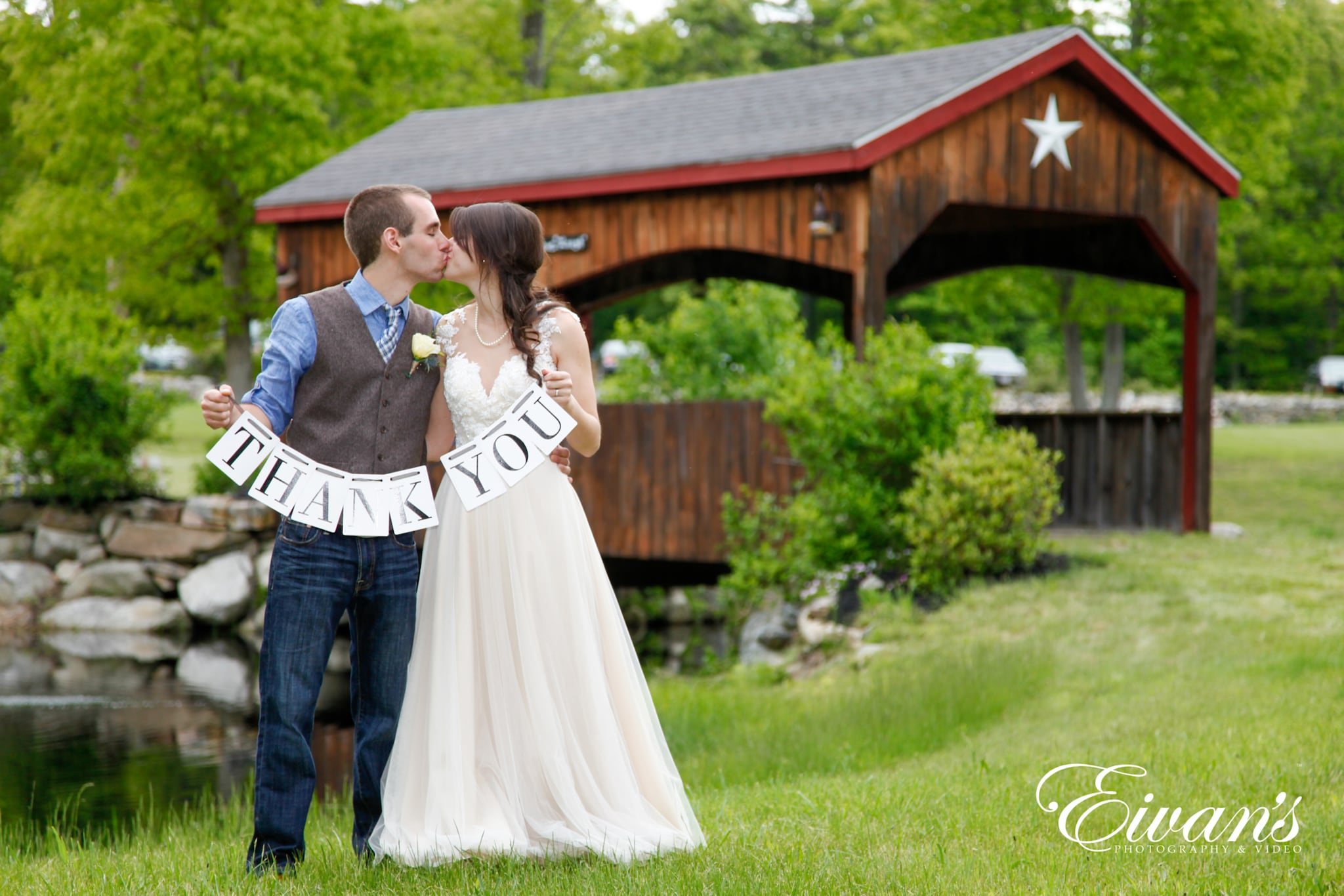 image of a bride and groom kissing while holding up a thank you sign